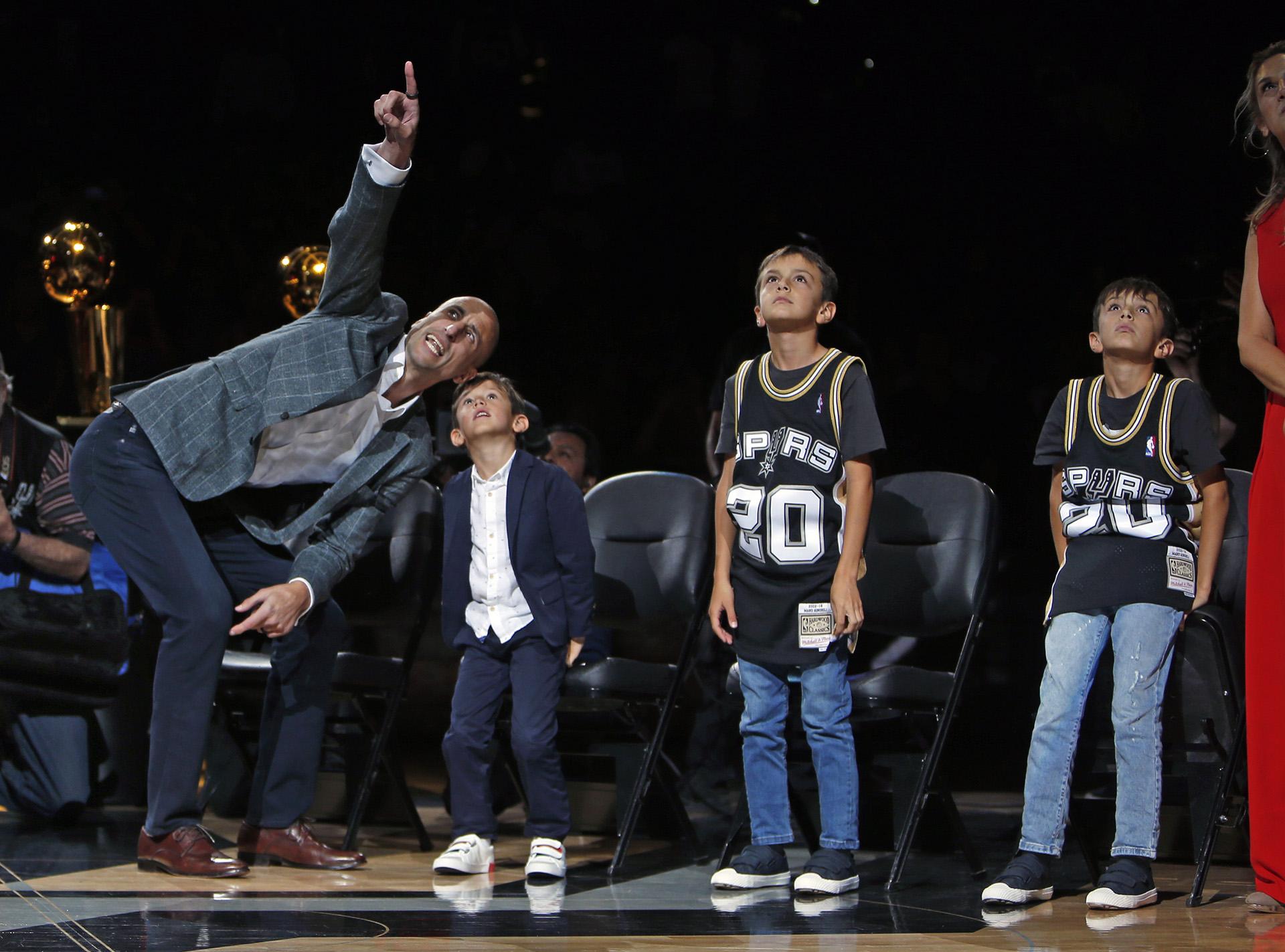 Manu Ginóbili ayuda a sus hijos a ver cómo su número llega a las vigas del AT&T Center en San Antonio
