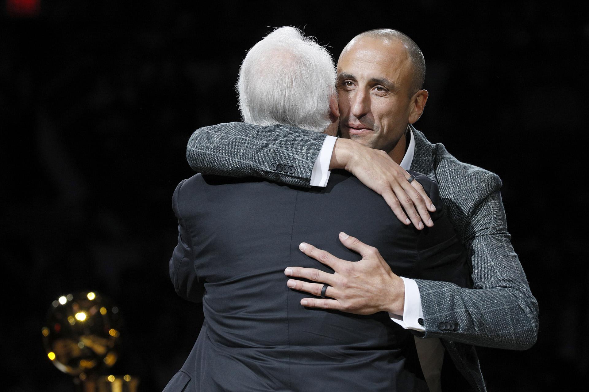 El ex jugador de los San Antonio Spurs, Manu Ginóbili (frente a la cámara), abraza al entrenador de los Spurs, Gregg Popovich, durante una ceremonia de retiro de su camiseta en el AT&T Center después de un partido entre los Cleveland Cavaliers y San Antonio Spurs