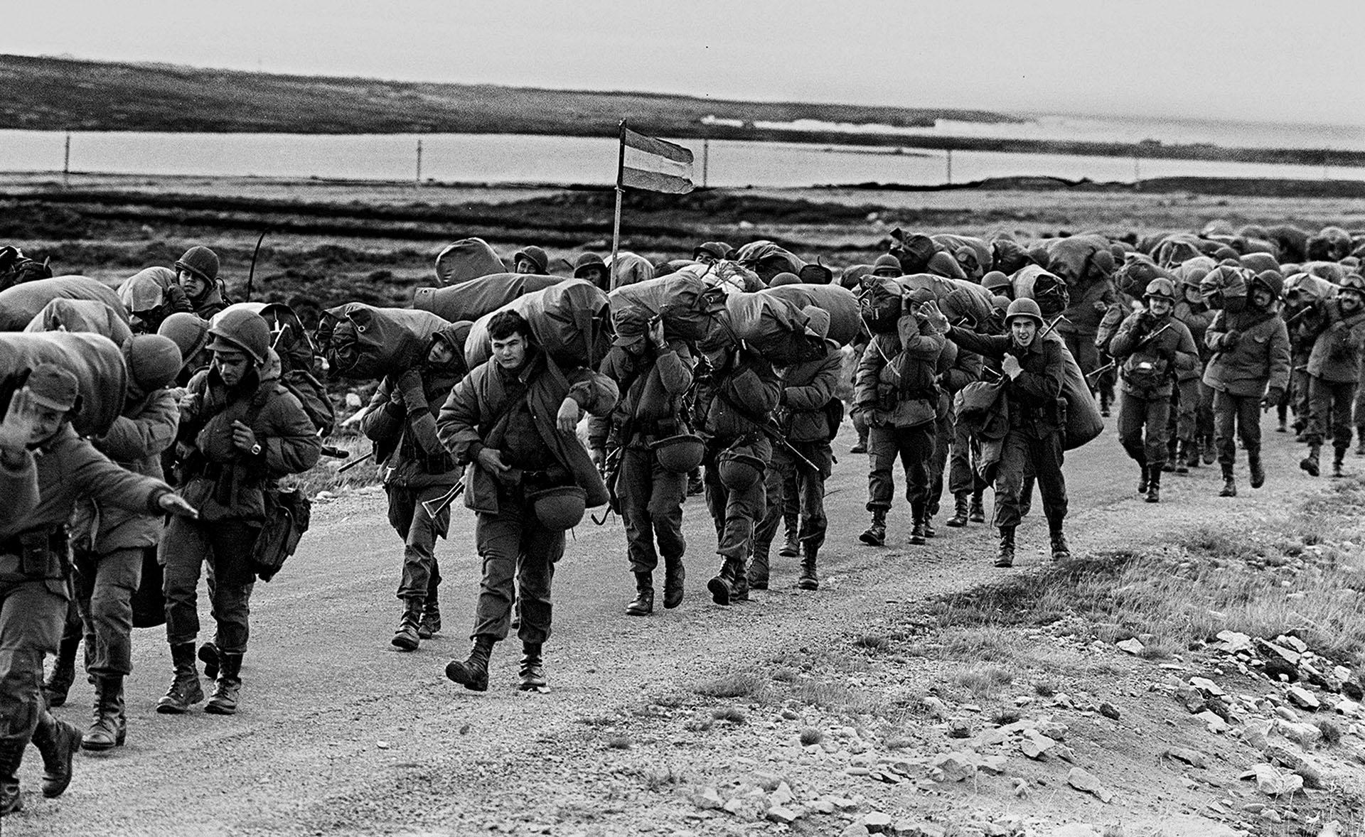 El esfuerzo y el frío se hacen sentir. El peso del equipo obliga a agachar la cabeza y avanzar. Algunos, hasta tienen tiempo para saludar y sonreír. Entreel pelotón, un soldado mantiene erguido al pabellón nacional.(Foto: AFP).