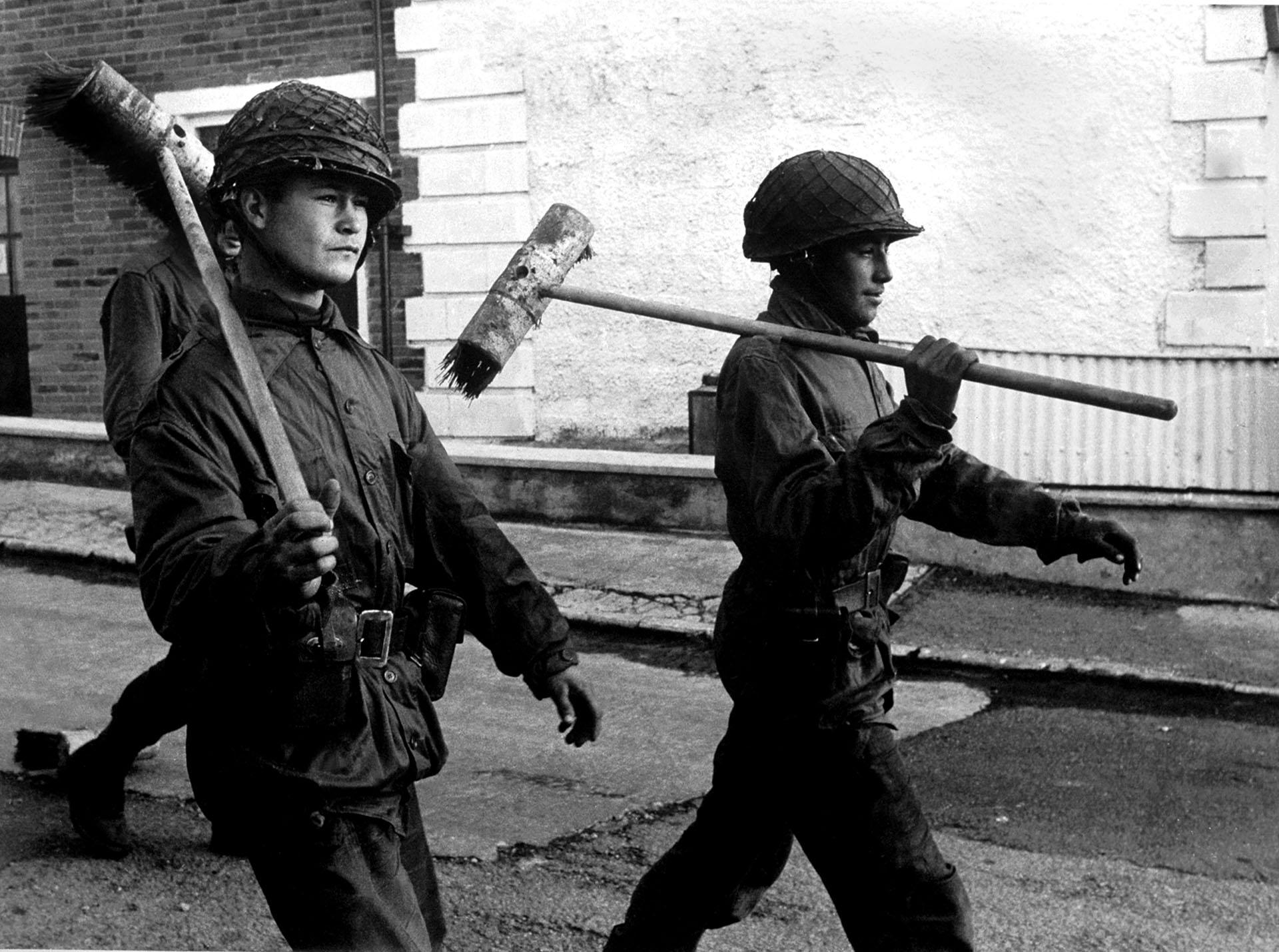 """Si bien son soldados que acaban de realizar una tarea de acción cívica, como mantener limpias las calles, para Eduardo Farré, el fotógrafo que captó la imagen, la cuestión pasa por otro lado:""""Es mi mirada sobre cualquier guerra. Los vi marchando con los escobillones al hombro como si fueran armas y me llamó la atención ese contraste con lo que se estaba viviendo""""."""