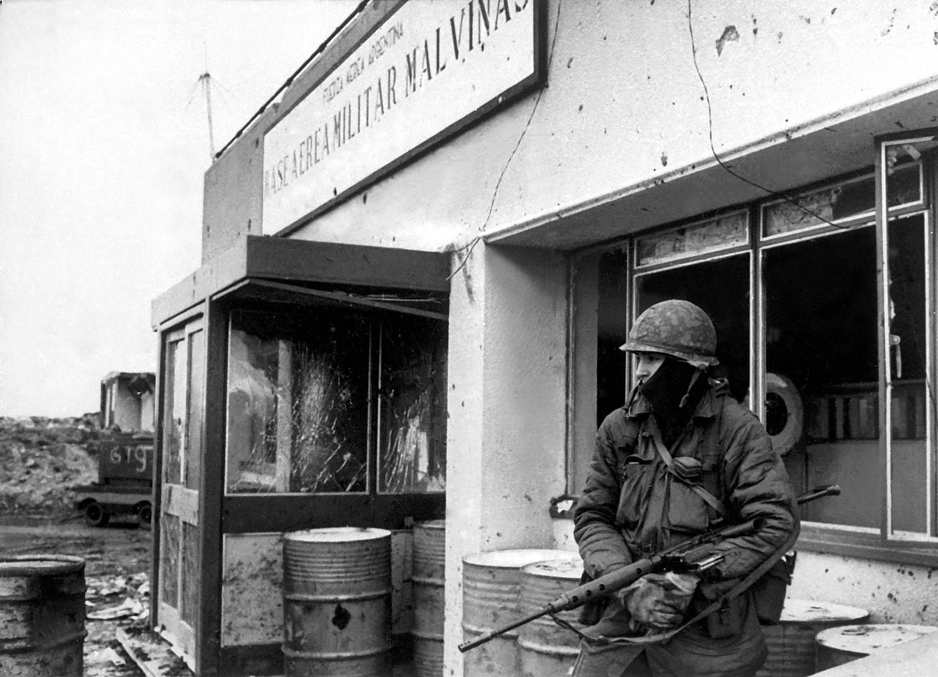 Estoico, en soledad, el soldado custodia la entrada de la Base Militar Malvinas. Los vidrios de las ventanas están hechos añicos o han desaparecido por los efectos de las bombas. Los tambores de gasolina le sirven como apoyo (Foto: Eduardo Farré).