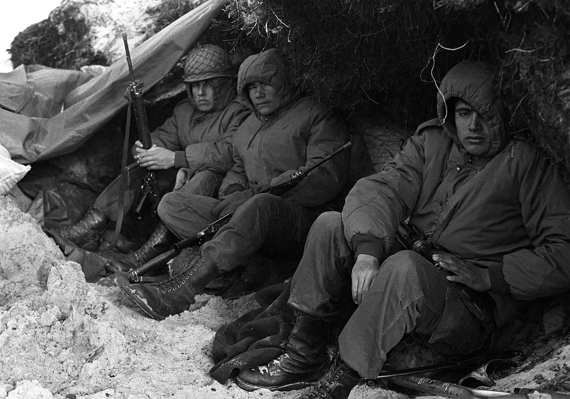 El frío está pegado en sus rostros. La naturaleza no ayuda. El clima es implacable. Medio adormilados, inexpresivos, con la nieve rozando sus botas y en una precaria posición, esperan los combatientes en su trinchera. (Foto: Telam / Román von Eckstein).