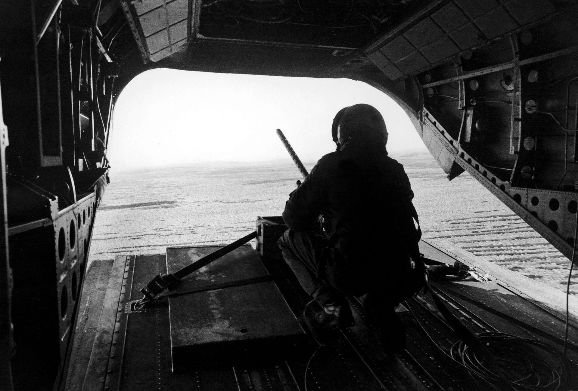 Desde la parte trasera de un helicóptero Chinook, vigila las posiciones argentinas durante un vuelo entre el estrecho San Carlos y Pradera del Ganso. El arma permanece fija en sus anclajes (Foto: Eduardo Farré).