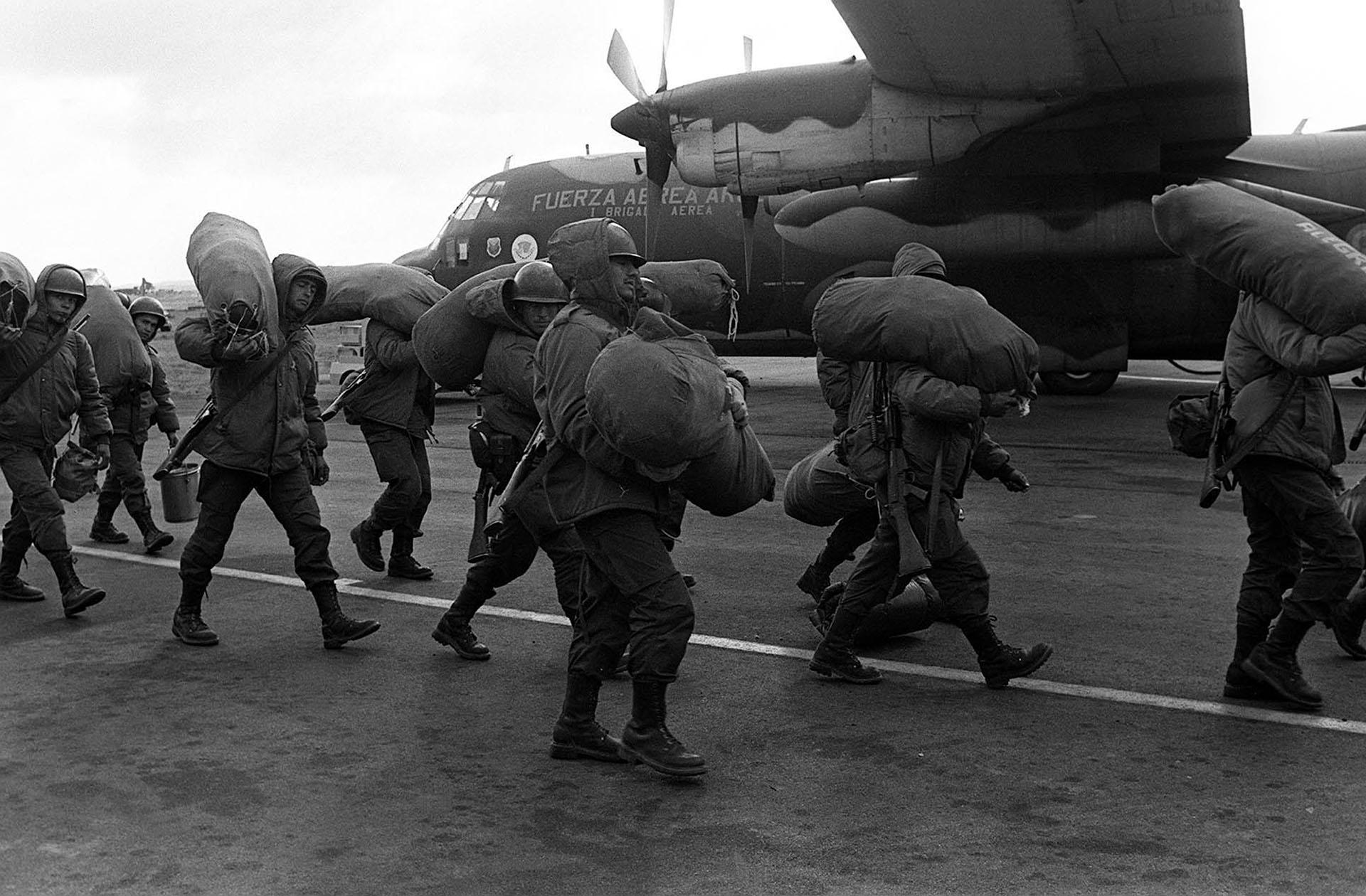 Una vez recuperadas las islas, un contingente de soldados se apresta a embarcarse rumbo a Malvinas. Para muchos será su primera experiencia en avión. El Hércules de la FuerzaAérea los espera. Bolsones al hombro y fusiles en bandolera, no falta hasta el baldepara el mate cocido (Telam / Román von Eckstein).