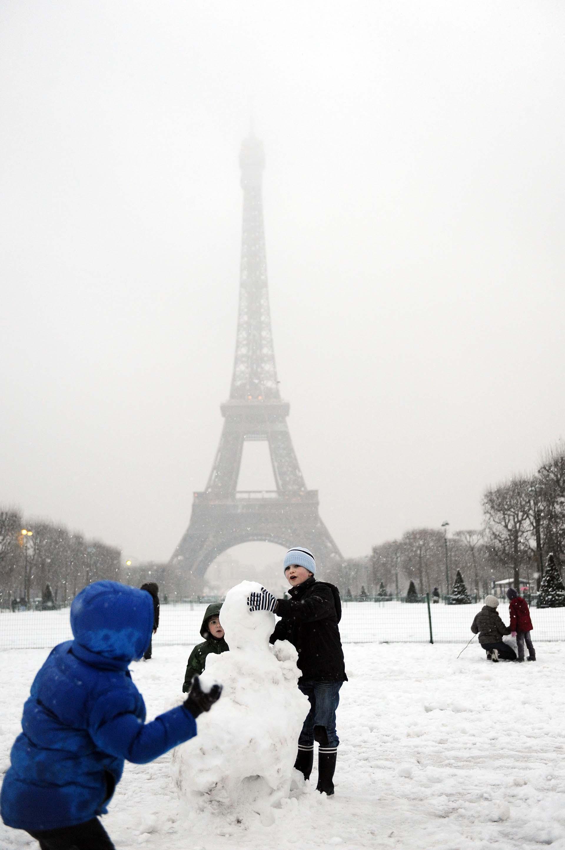 Niños hacen un muñeco de nieve frente a la Torre Eiffel durante una de las habituales tormentas de nieve invernales en Paris.