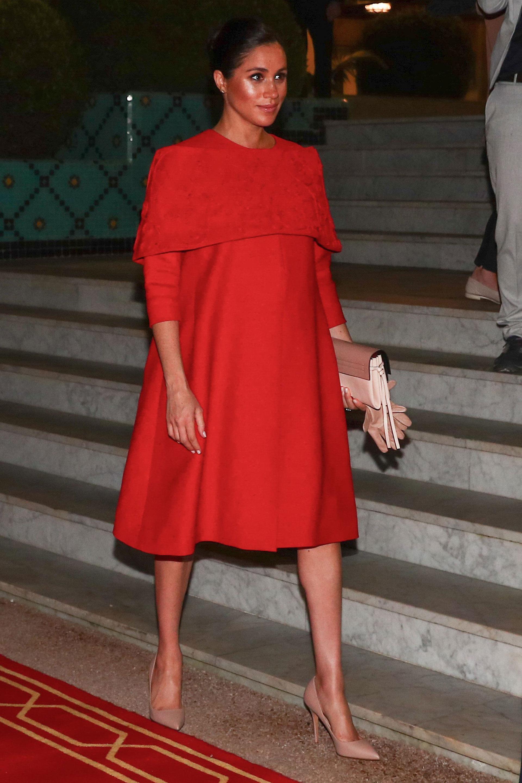 Meghan comenzó su gira real marroquí con un vestido rojo de capa de Valentino para su llegada al aeropuerto de Casablanca. La duquesa combinó el look con tacones y guantes color nude y un clutch Valentino Garvani (AP)