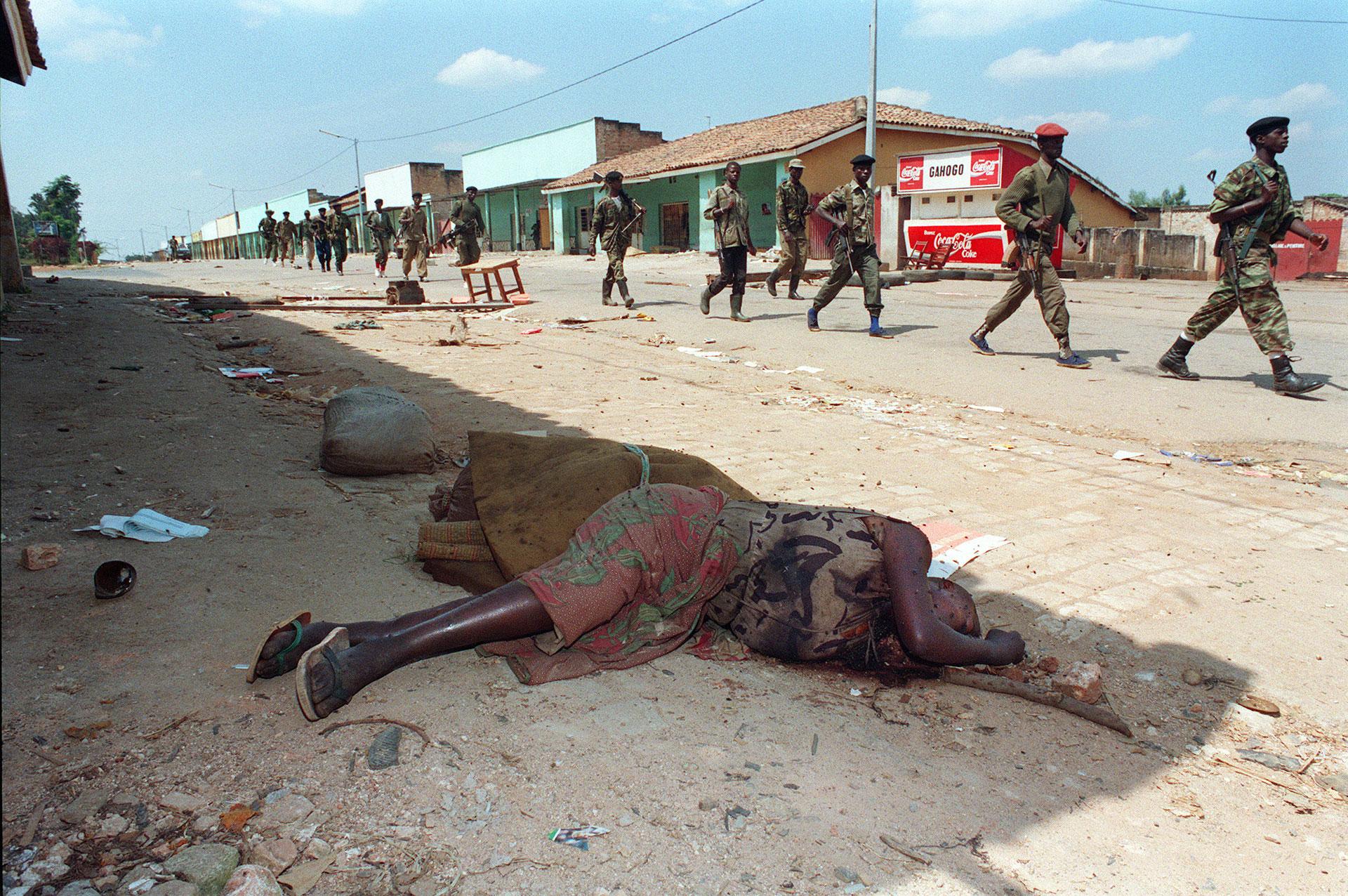 Combatientes del Frente Patriótico caminan el 16 de junio al lado del cuerpo de una mujer asesinada días antes por hutus (AFP)