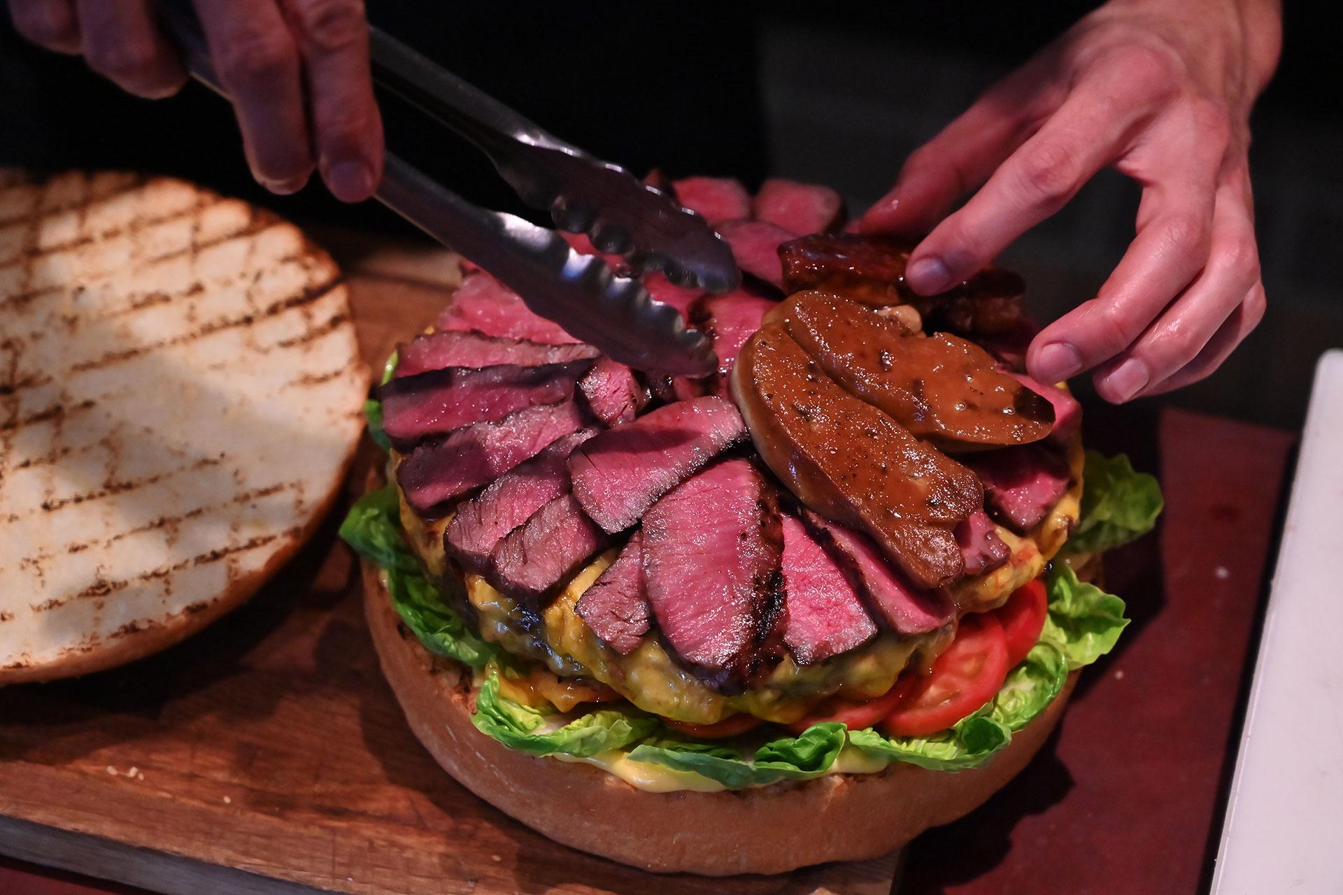 Shimada coloca las láminas de carne sobre la hamburguesa