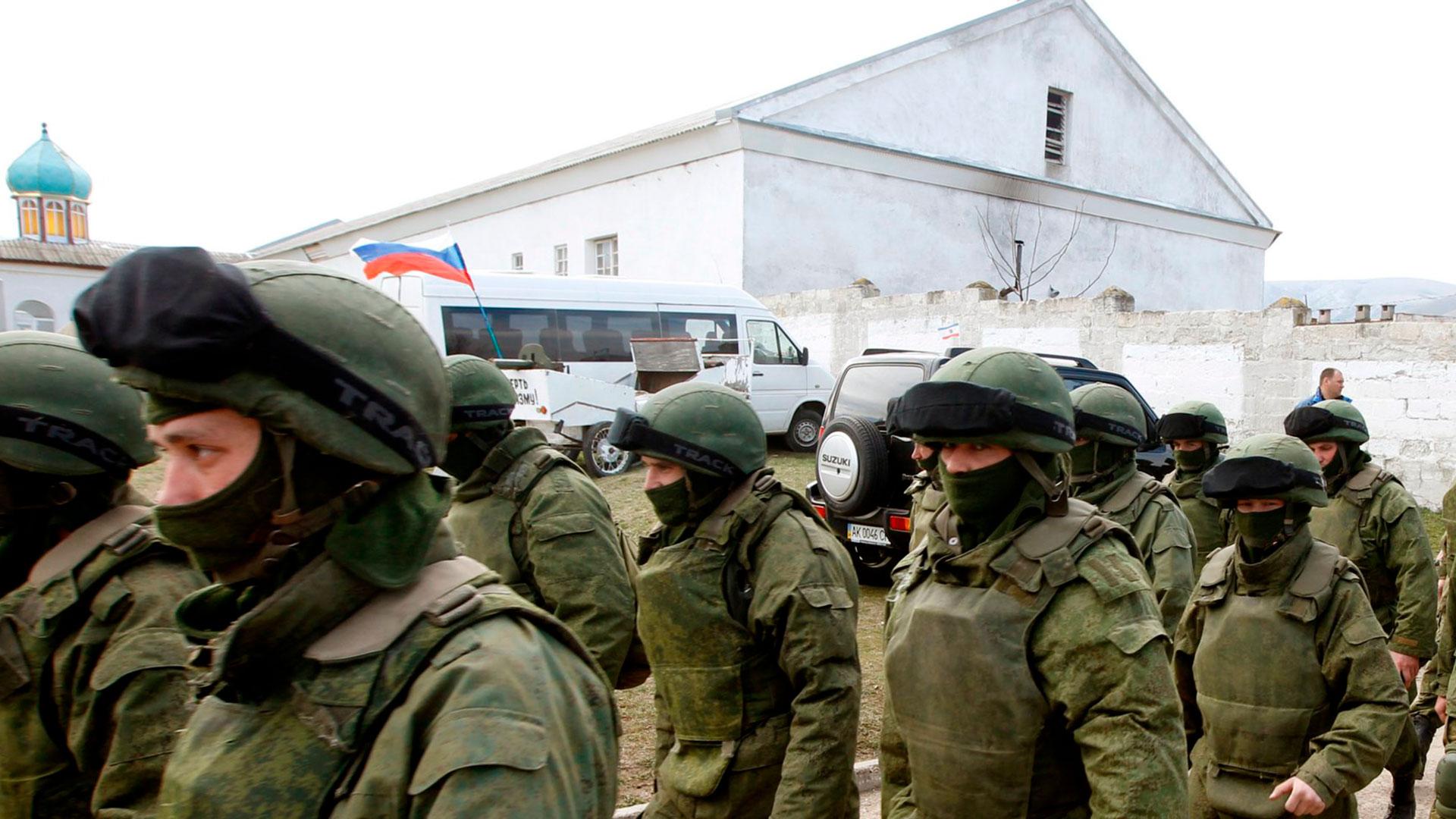 Hombres armados, presuntamente militares rusos, salen de una base militar ucraniana en Perevalnoye, cerca de la ciudad de Simferopol, en Crimea, el 14 de marzo de 2014.