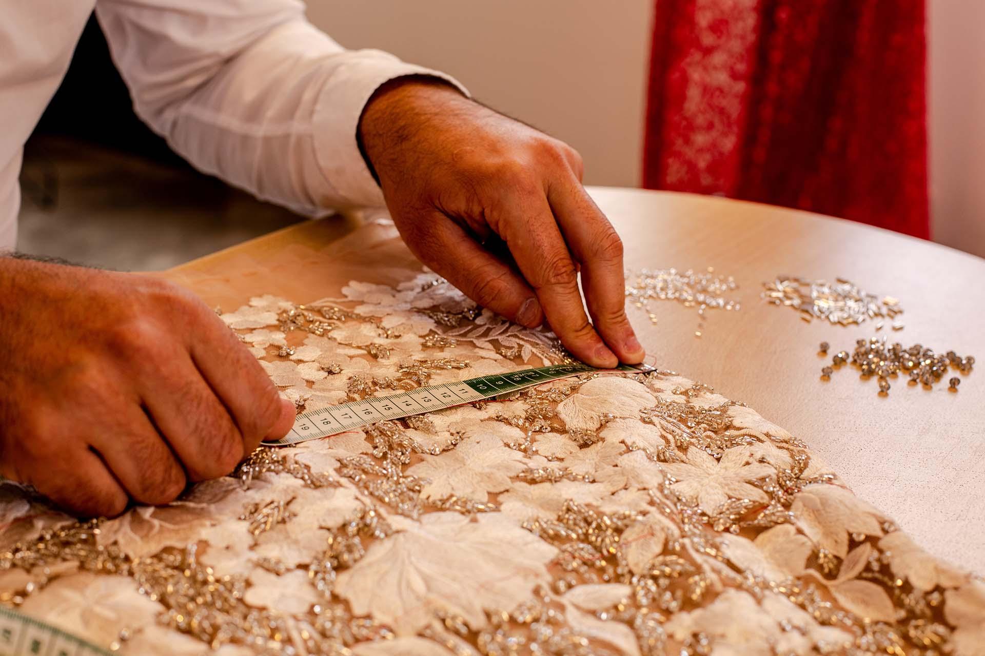 Sobre pieza de noche realizada a medida en transparencia nube y encaje, Gabriel marca la posición donde deben ser incrustados cada uno de los hilos de seda que se realizaron en una máquina de una sola aguja guiada totalmente a mano.
