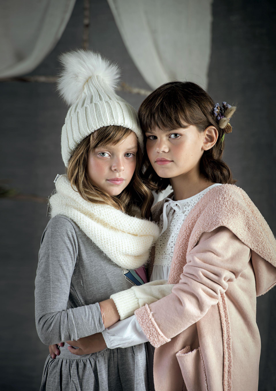 Oli: Vestido de algodón(Grisino), cuello de lana y gorro con pompón(Todo moda). Nina: tapado gamuzado( Stai Zitta) y remera con pechera de broderie(Mimo & Co).