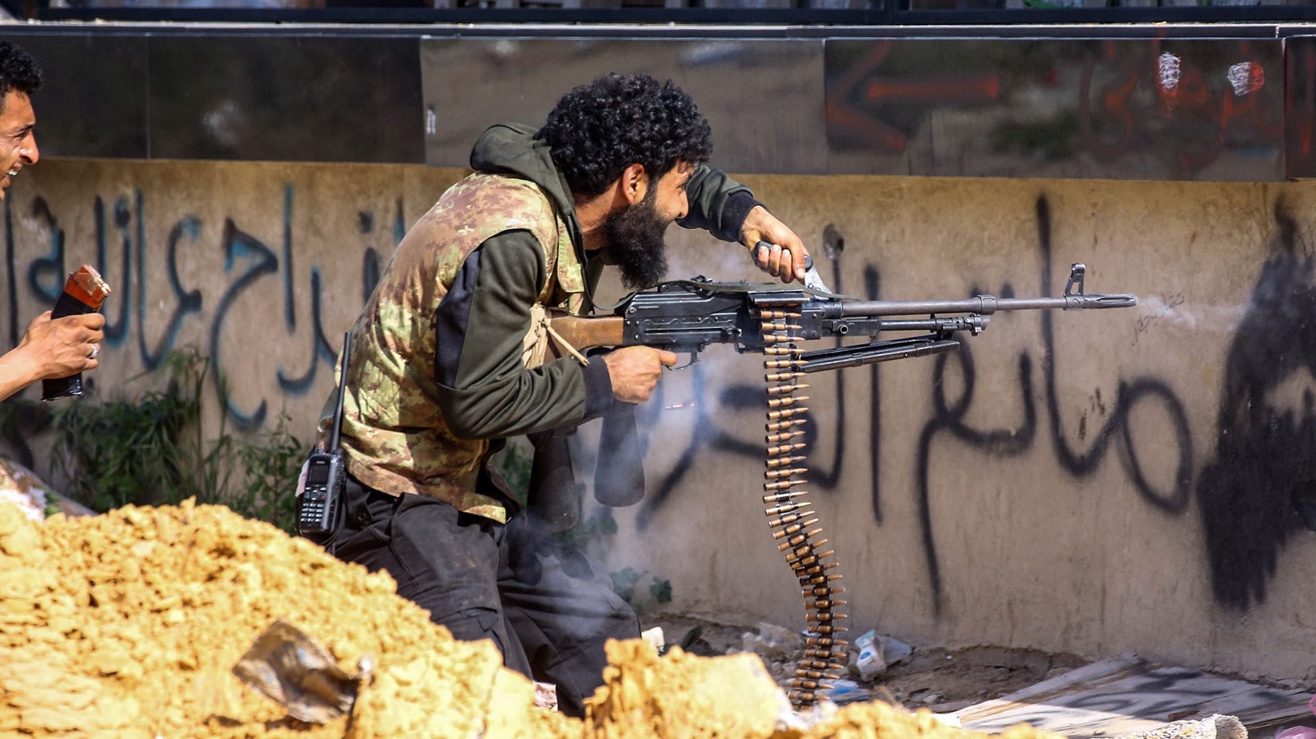 Un combatiente leal alGNA dispara una ametralladora durante los enfrentamientos con las fuerzas de Haftar en el suburbio de Aoli Zara, en Trípoli, el 10 de abril (AFP)