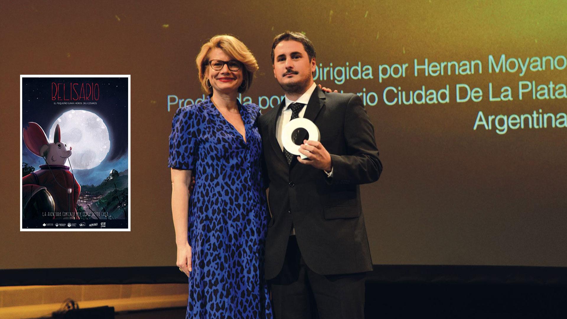 Hernán Moyano recibe el premio en las españolas Islas Canarias. Al lado, el afiche de Belisario, el pequeño gran héroe del cosmos: un ratón que se convirtió en león.
