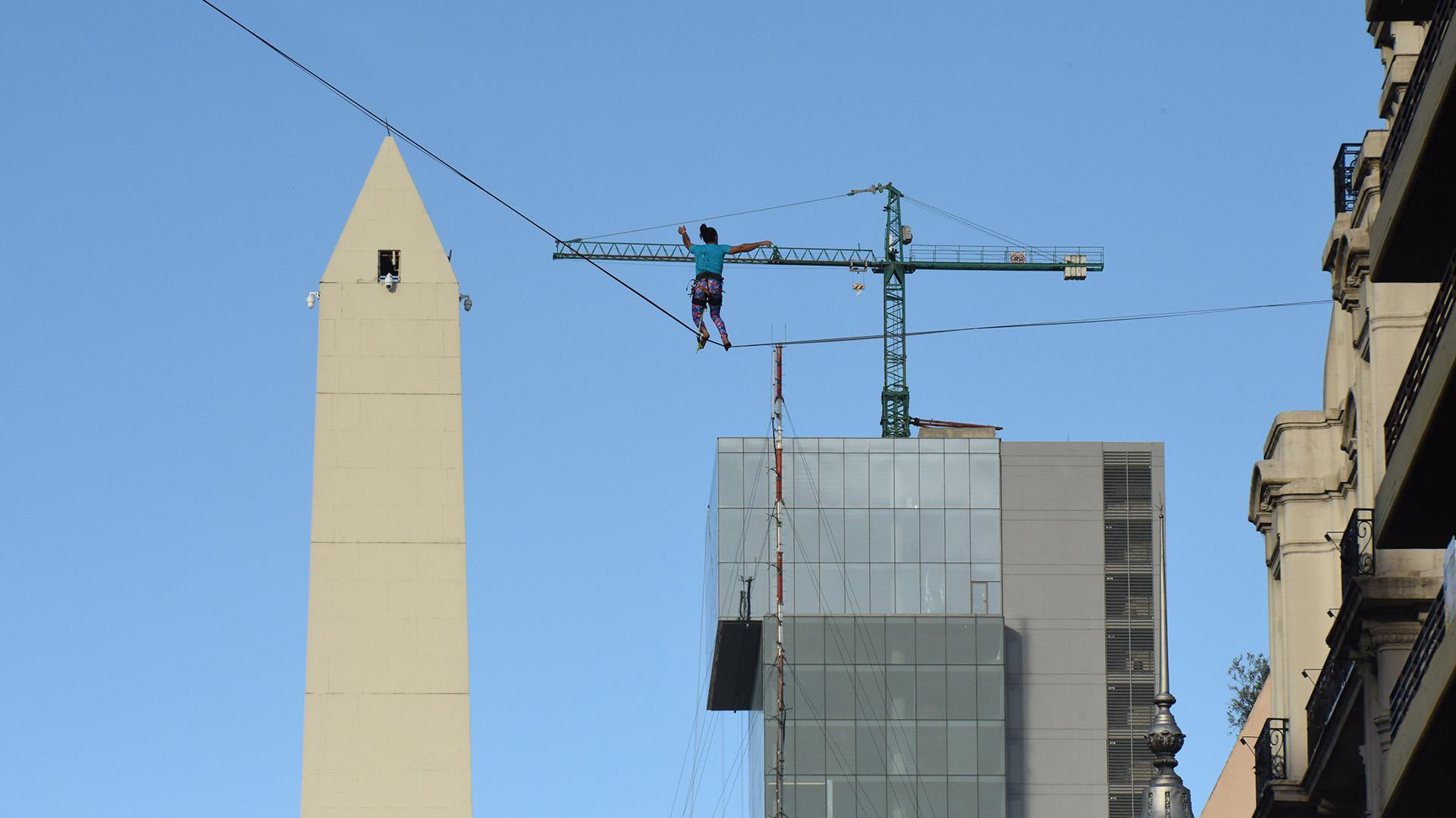 Una mujer haciendo equilibrio con el Obelisco de fondo
