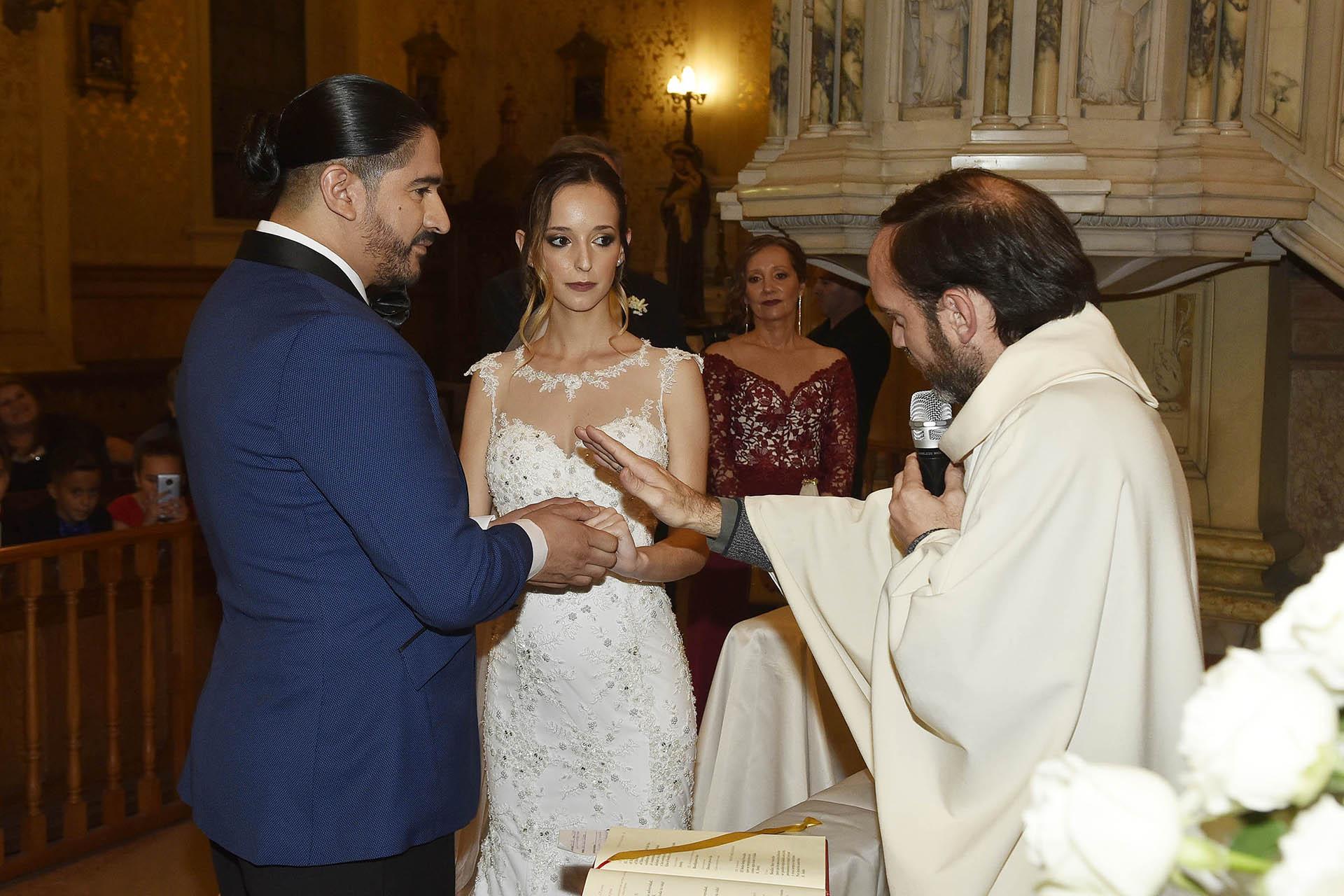 El cura bendiciendo los anillos de matrimonio de Ariel Puchetta y Camila Minoldo