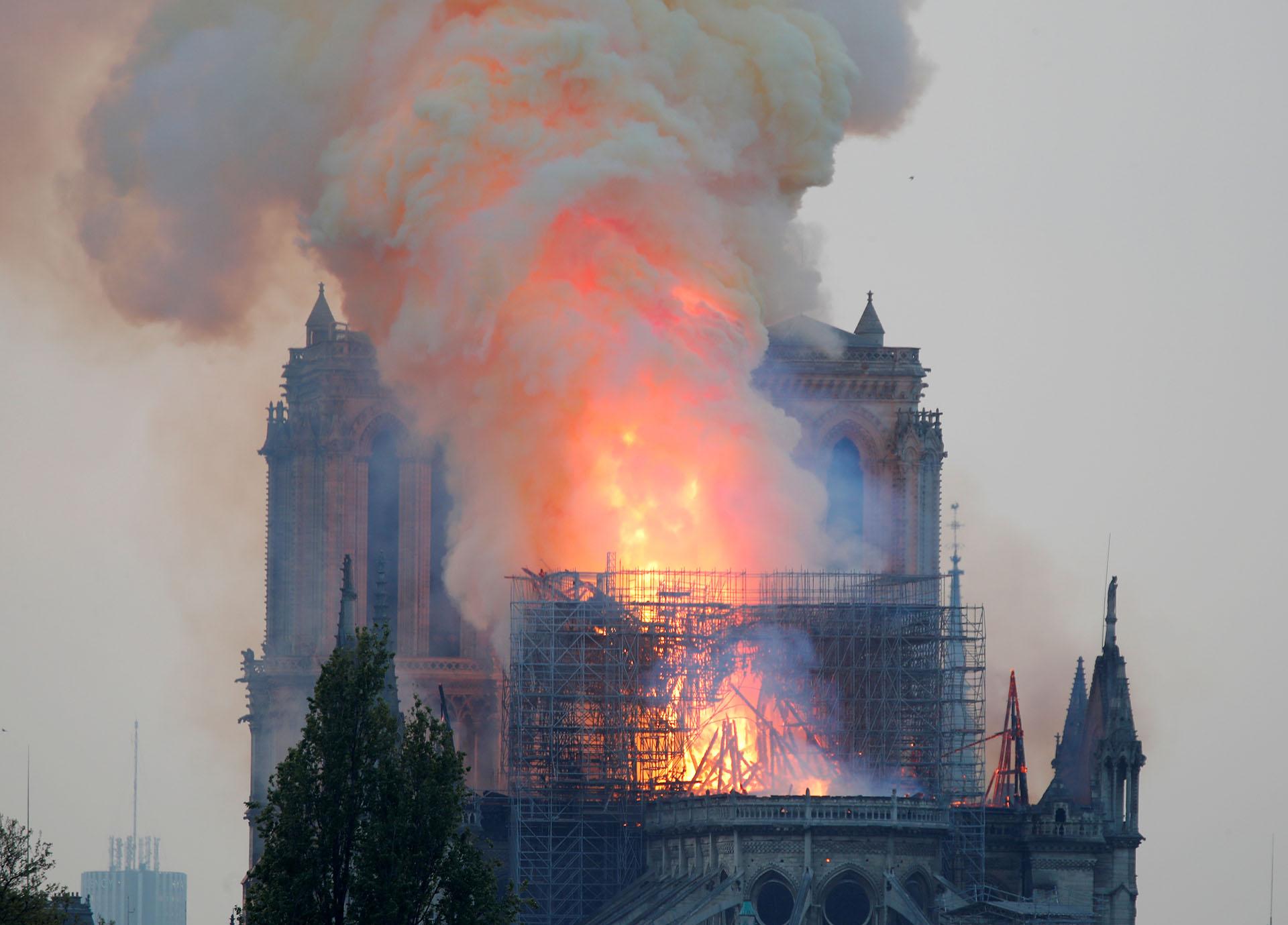 El fuego provocó el derrumbe de la aguja de la torre principal y de la estructura completa del techo, ante la impotencia de los bomberos, que no logran llegar al epicentro del incendio (Foto: REUTERS/Charles Platiau)