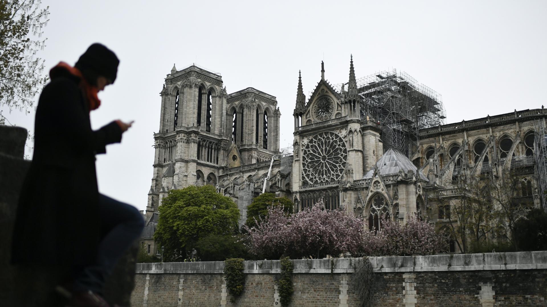 Una personas cerca la catedral un días después del incendio. (AFP)