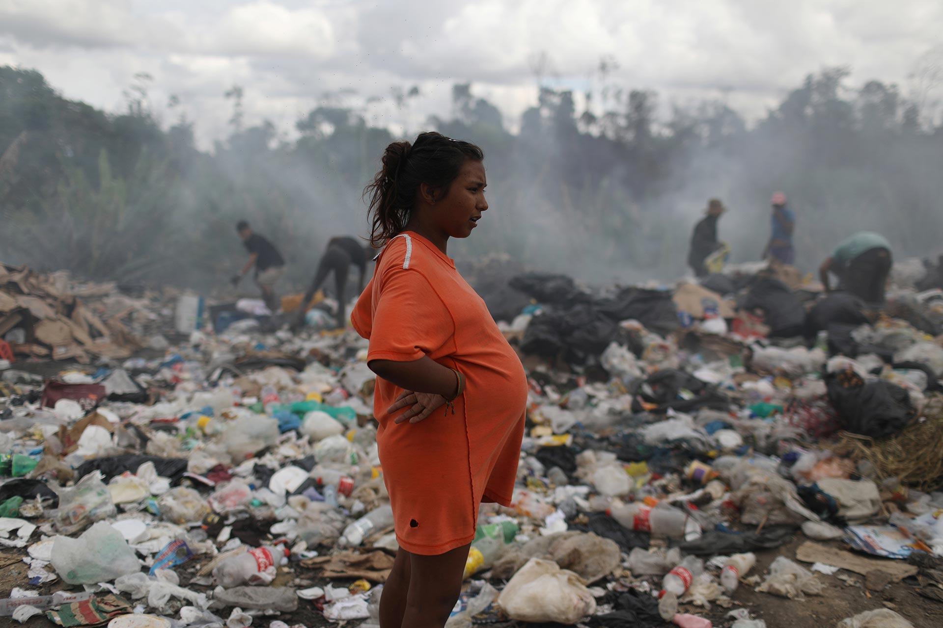 Una mujer embarazada de 8 meses también revuelve la basura (REUTERS/Pilar Olivares)