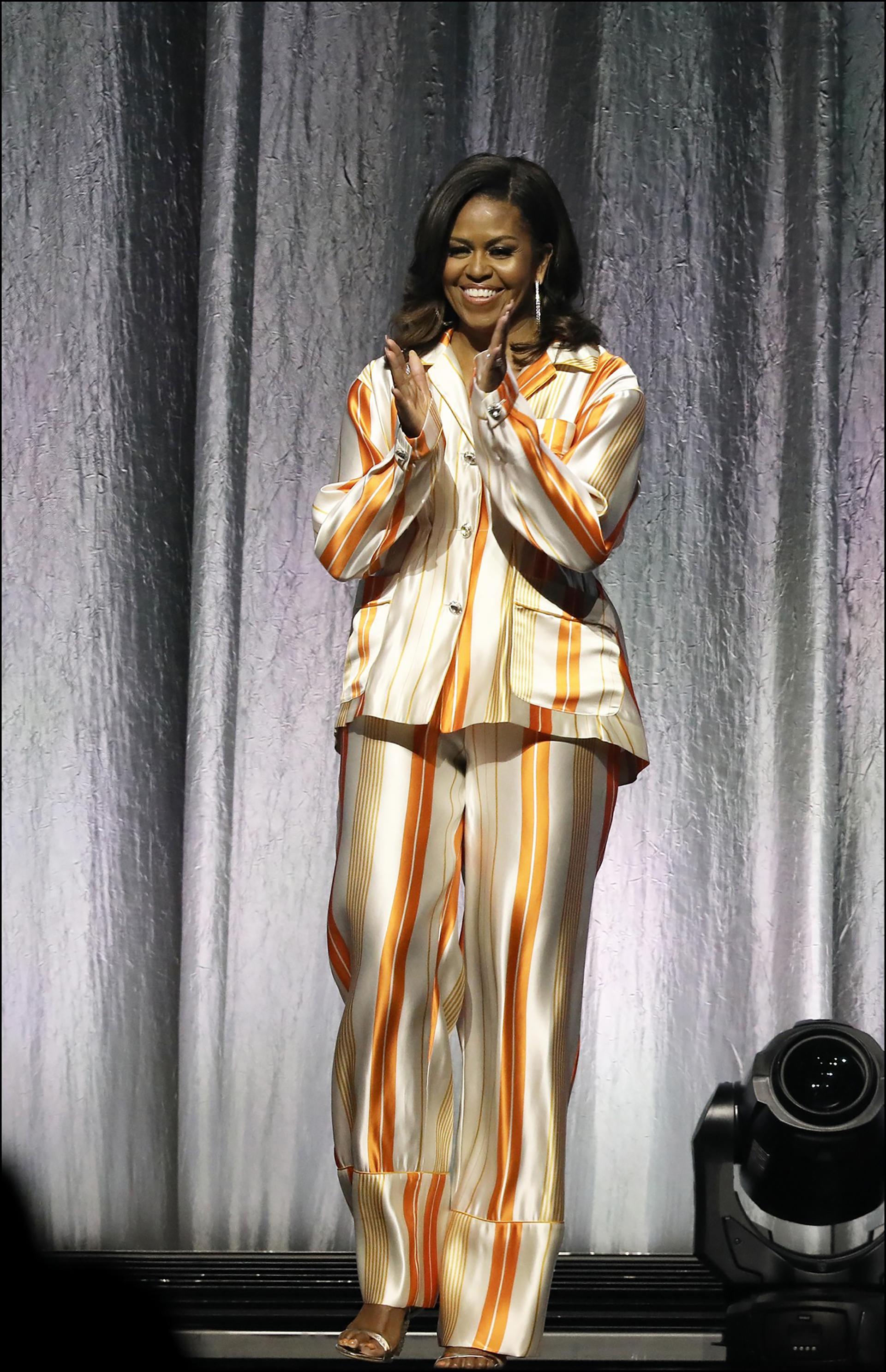 """En un traje de seda blanco a rayas naranjas, de corte masculino, la mujer de Barack Obama se lució como una mujer """"trendy""""."""