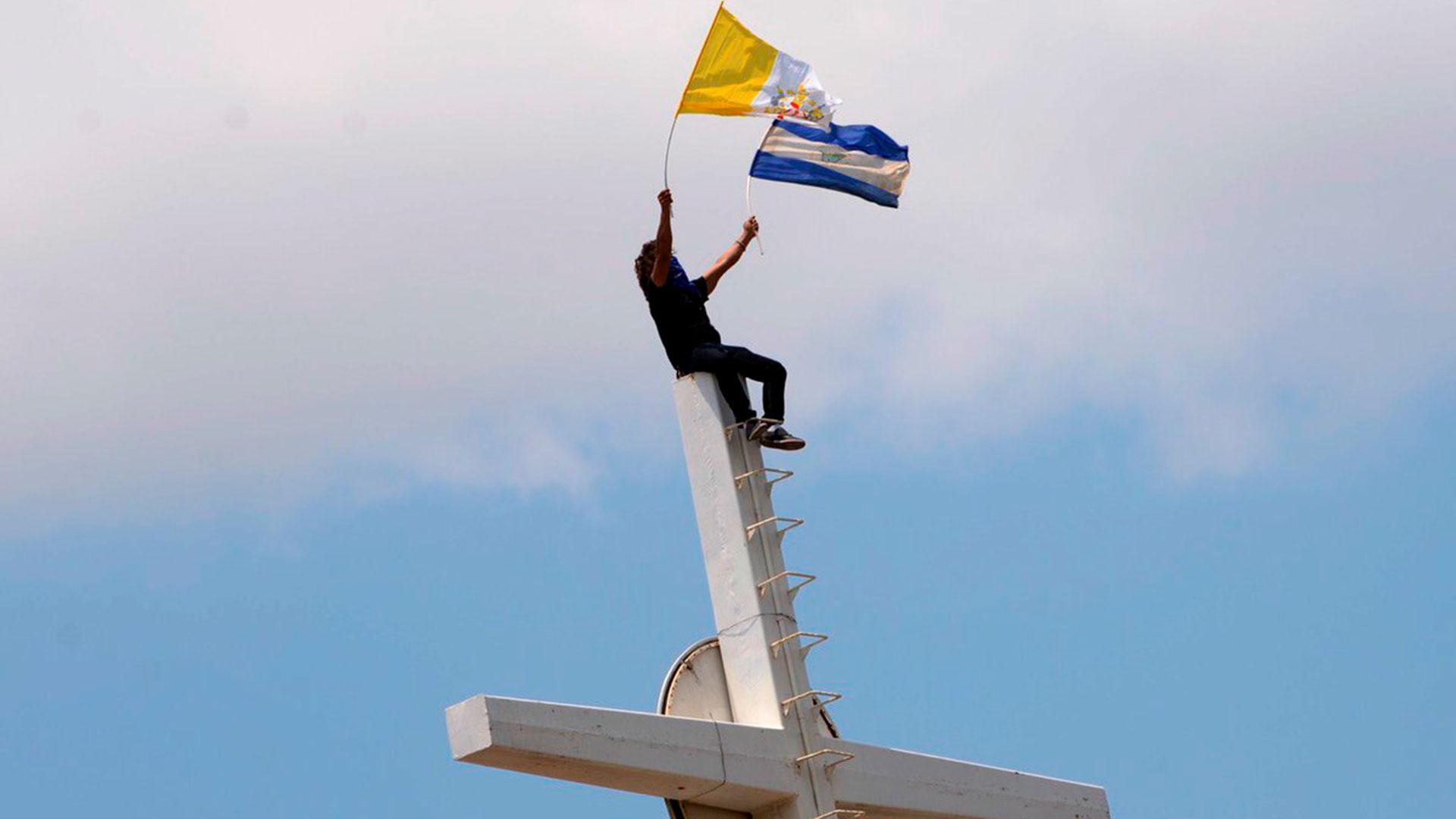Un manifestante ondea las banderas de Nicaragua y el Vaticano