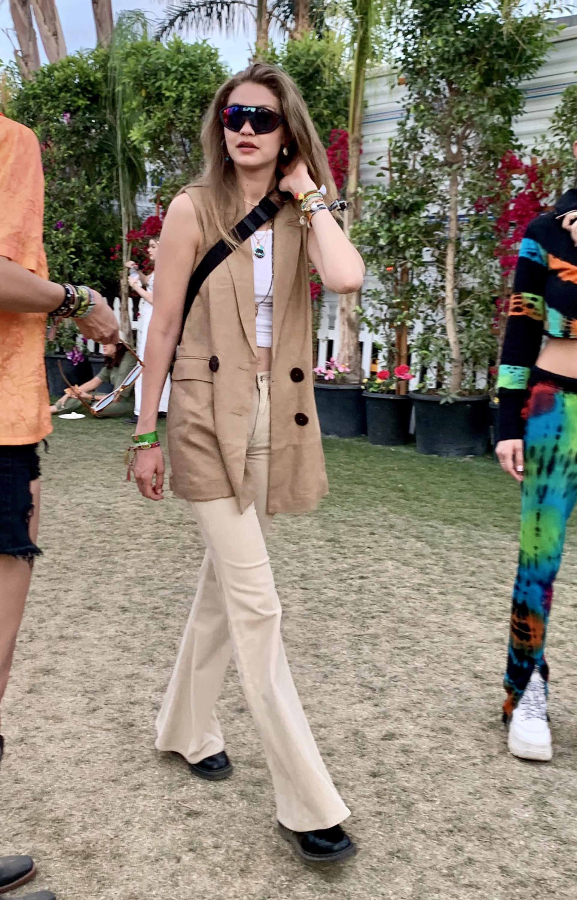 Gigi Hadid no se quiso perder el festival más top de California y apostó a un look más safari. Un chaleco de gamuza con maxi botones en marrón, un top blanco y pantalones de gabardina. Completó su look con pulseras de hilo y anteojosXL tornasol espejados