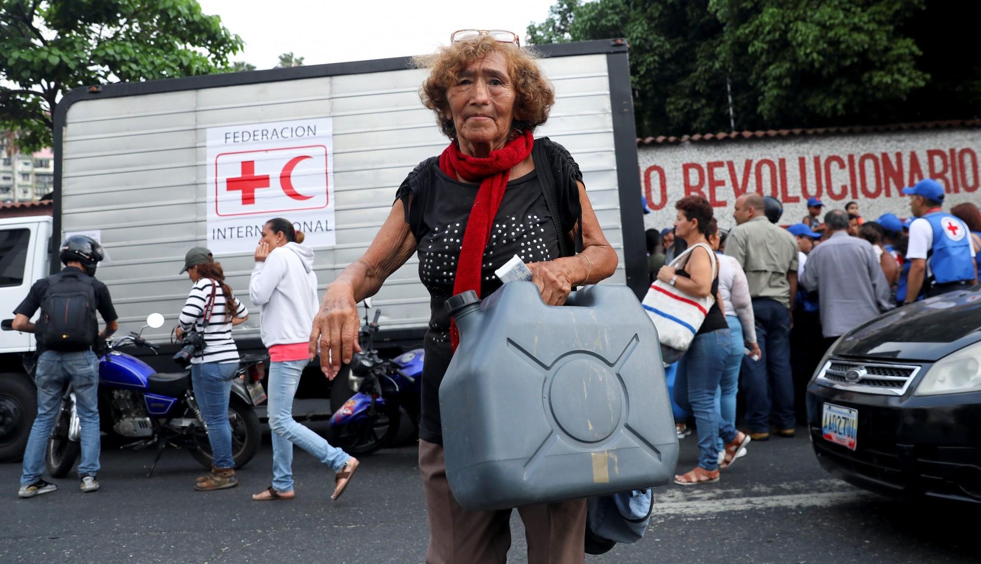 Una mujer carga un envase para agua repartido por la Cruz Roja (Reuters)