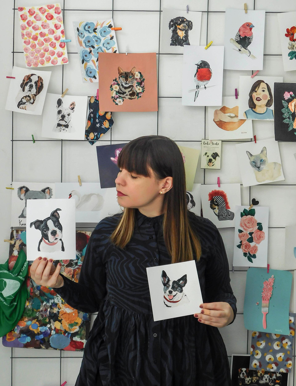 Luli Katz rodeada de retratos deanimales, colgados en las paredes de su estudio.