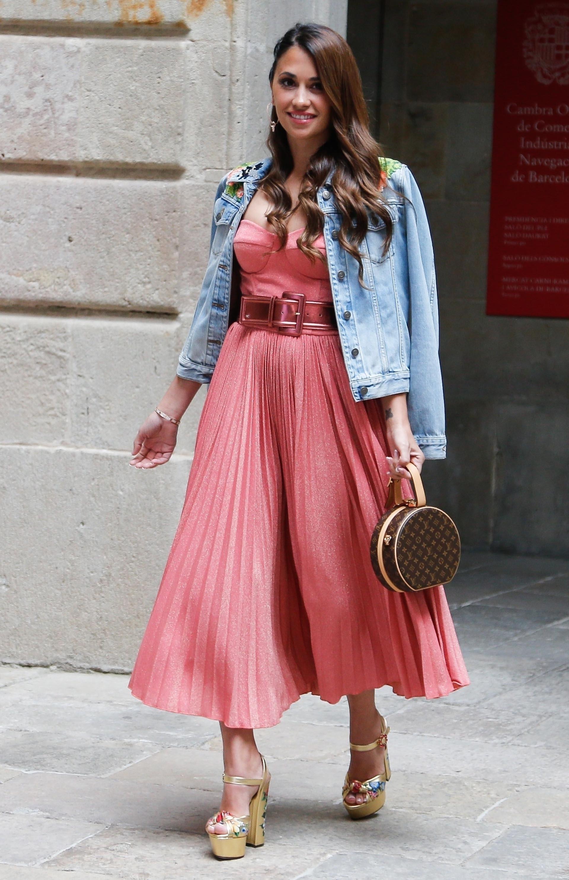 La esposa de Lionel Messi apostó por un vestido strapless plisado con cinturón metalizado, con campera de jean, una mini bag de Louis Vuitton, sandalias doradas pintadas a mano y completó el look con delicadas joyas doradas