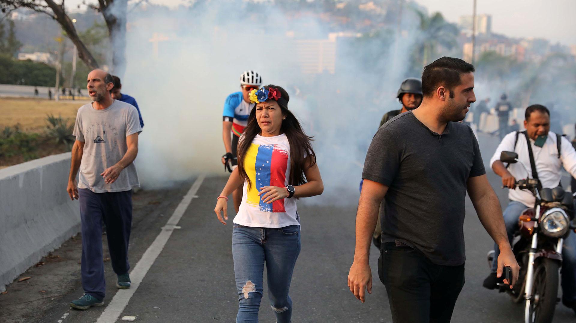 Una venezolana huye de los gases lacrimógenos lanzados por las fuerzas chavistas. (REUTERS/Manaure Quintero)