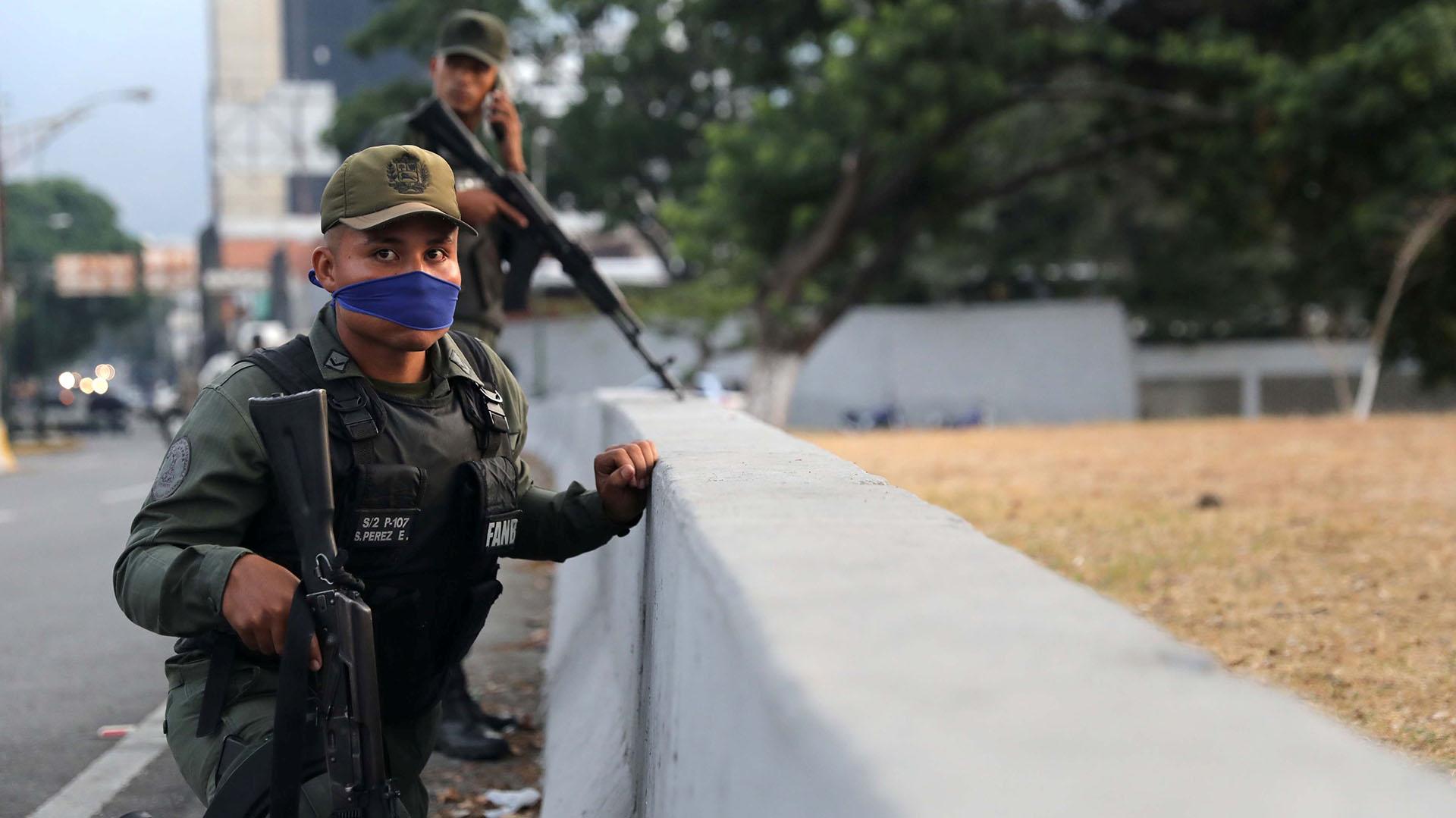 """Un soldado cerca de la base aérea """"La Carlota"""" coloca la cinta azul que lo identifica como leal a Juan Guaidó en su boca mientras espera la represión de las fuerzas chavistas."""