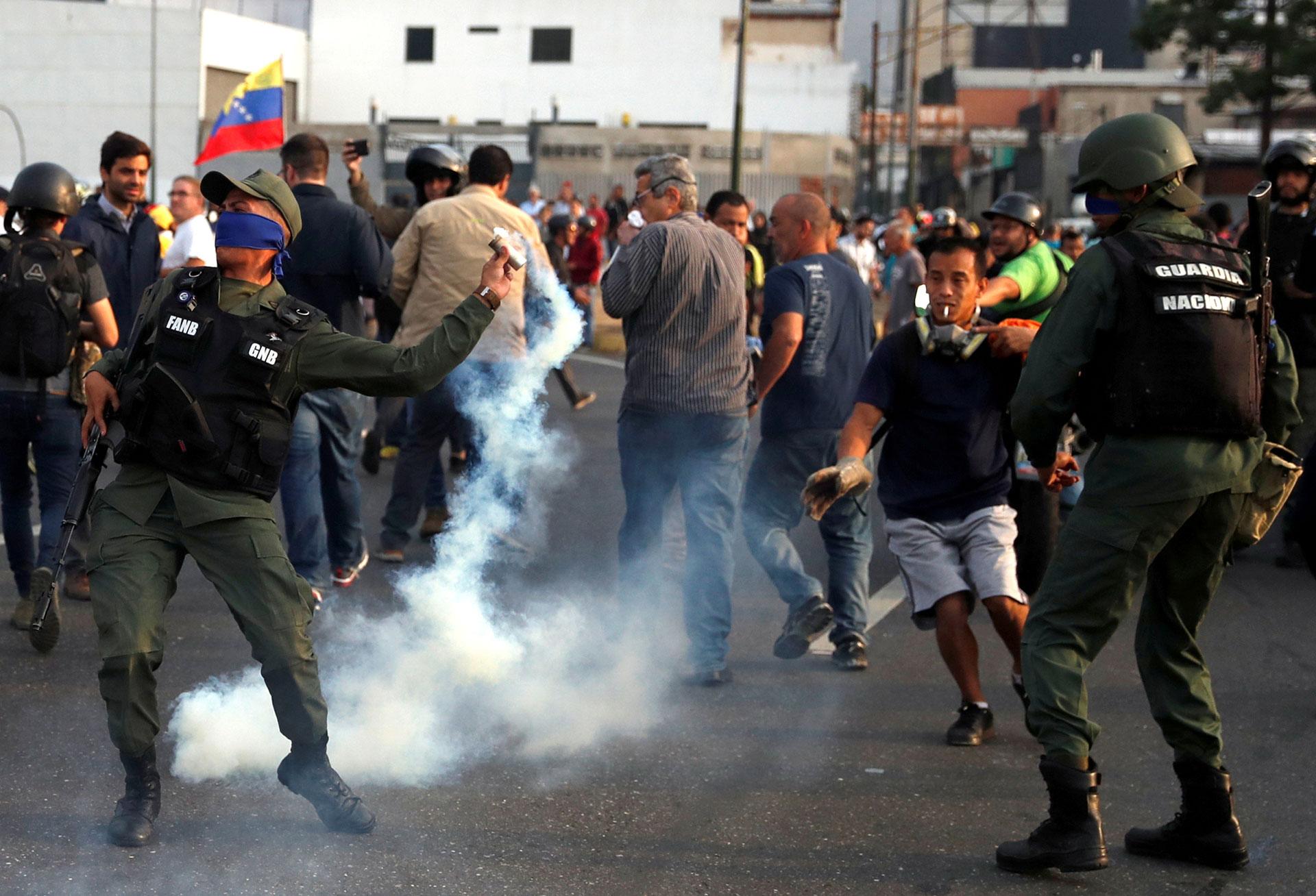 Un miembro de la Guardia Nacional leal a Juan Guaidó devuelve una bomba de gas lacrimógeno lanzado por las fuerzas chavistas para reprimir.