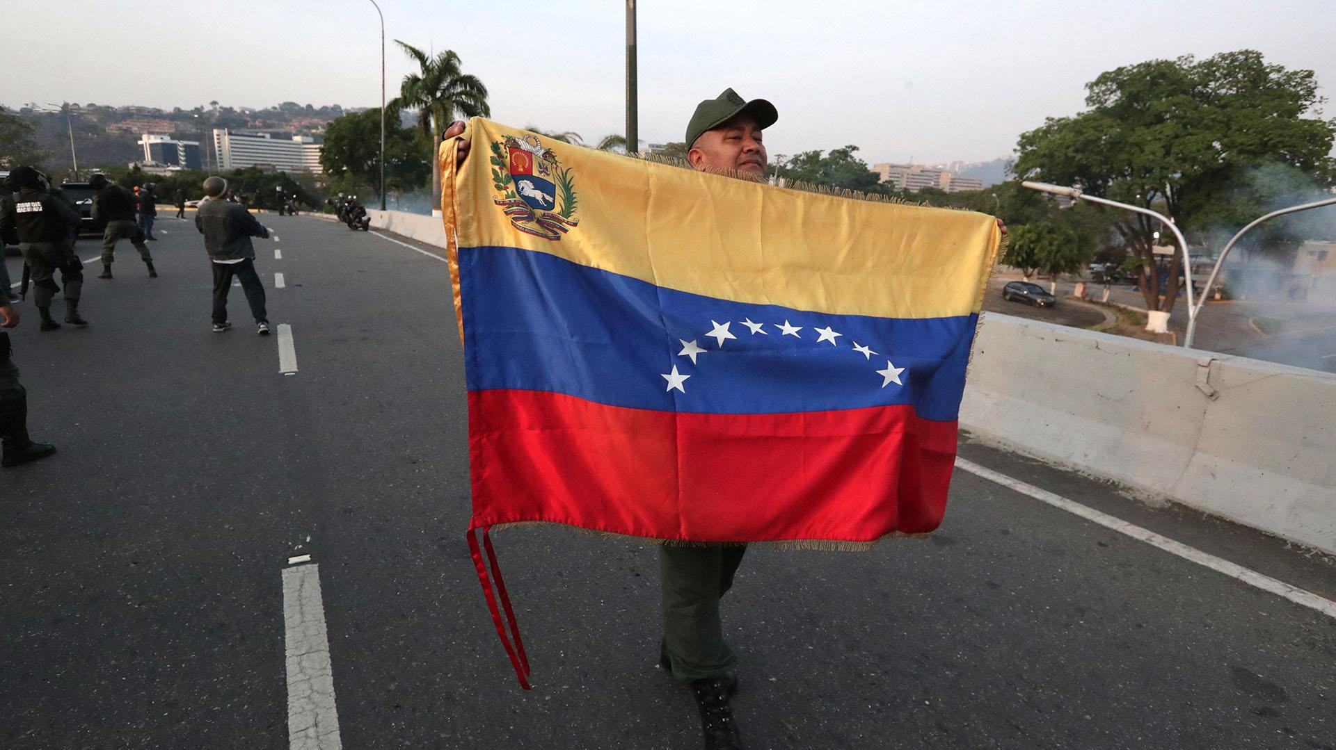 Un militar despliega una bandera en la base de La Carlota, al este de Caracas, donde ha sido conducido el opositor Leopoldo López, tras ser liberado este martes y donde se ha reunido con el presidente Juan Guaidó, que ha anunciado que los militares han dado el paso para unirse a él.