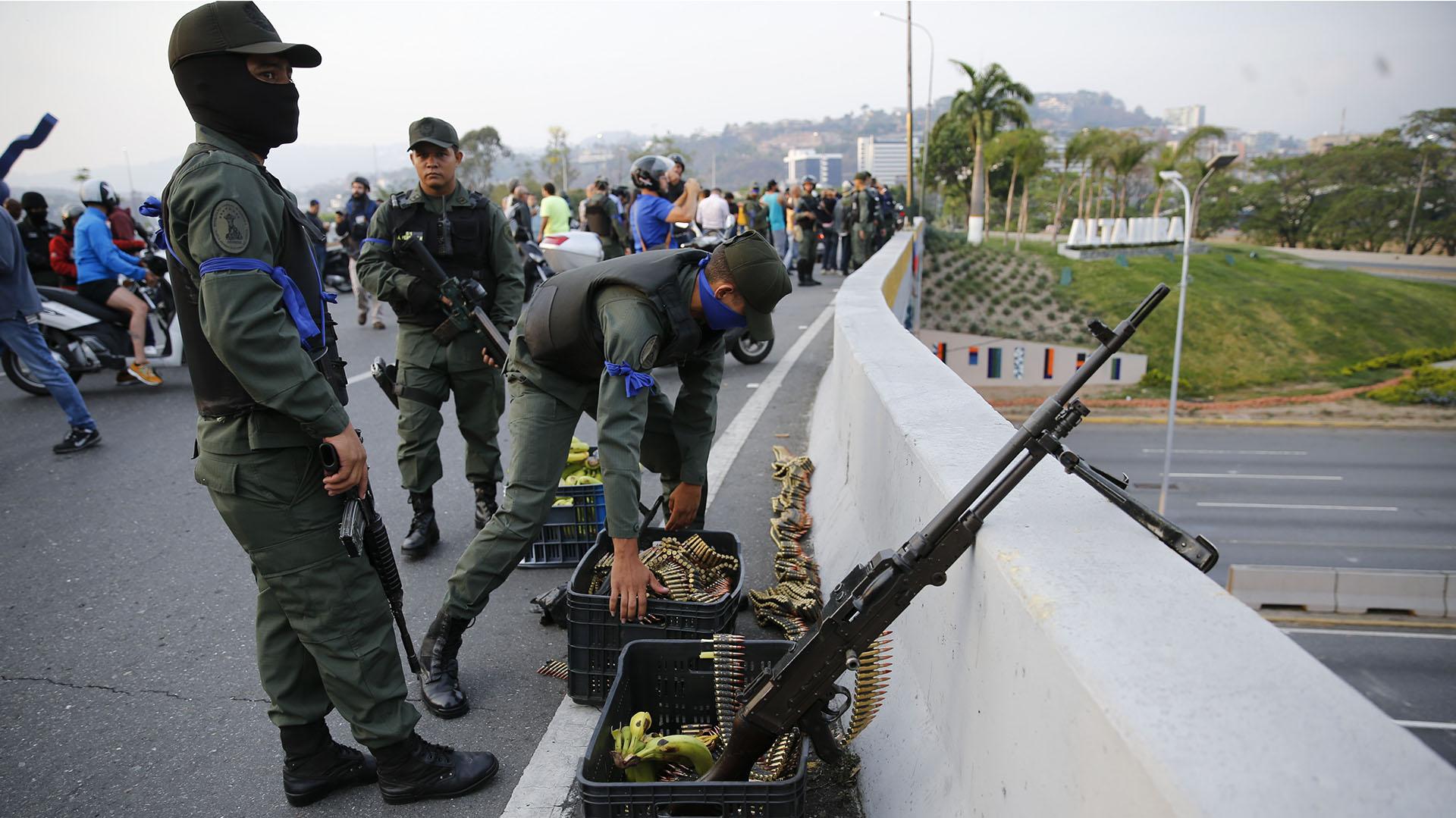 Los soldados de Juan Guaidó, que pueden ser identificados por la cinta azul en el brazo, se refugian en una autovía. (AP Photo/Ariana Cubillos)
