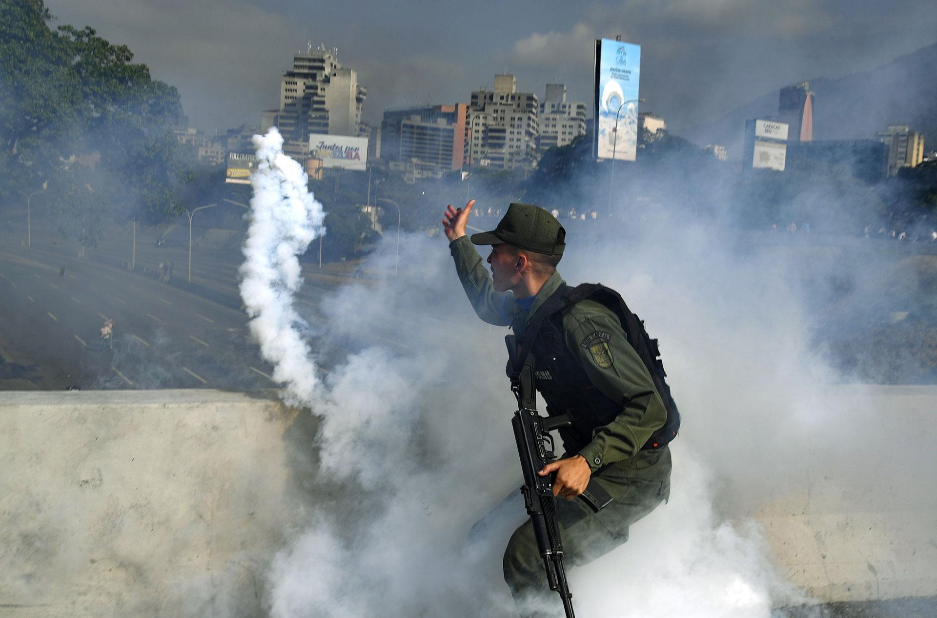 Un miembro de la Guardia Nacional Bolivariana que apoya al presidenteinterino Juan Guaidó lanza una lata de gas lacrimógeno durante un enfrentamiento con guardias leales al régimen de Nicolás Maduro frente a la base militar La Carlota.