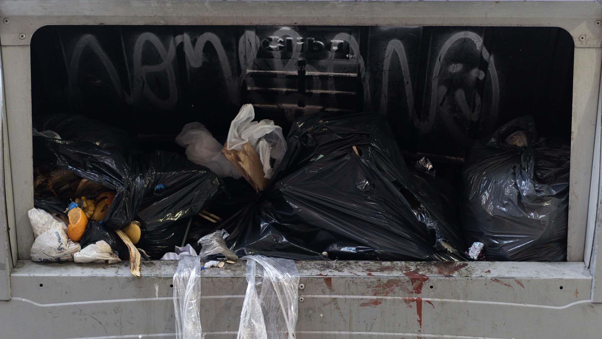 Restos de comida y bolsas de consorcio en uno de los volquetes de basura.