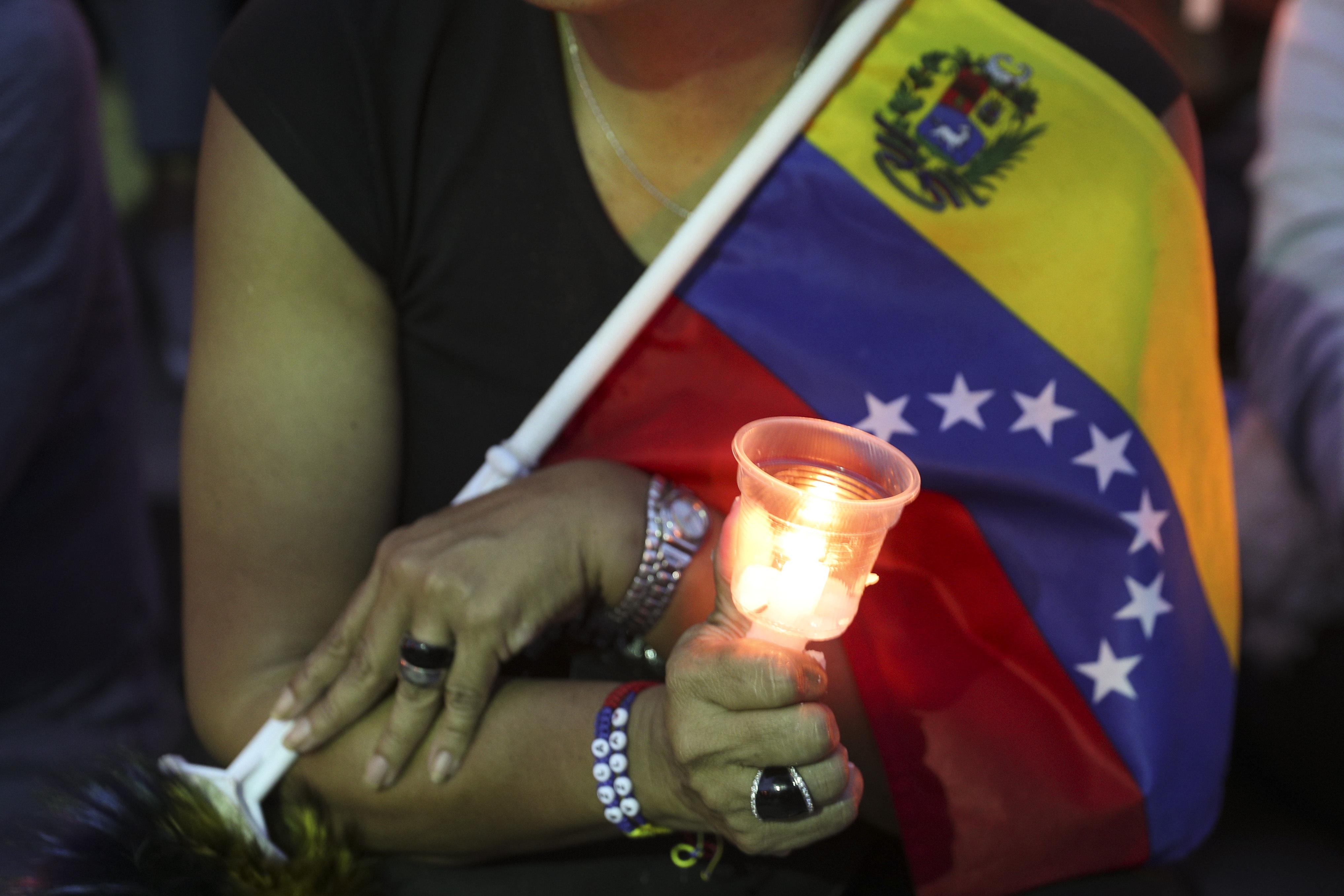 Una opositora al Gobierno del presidente Nicolás Maduro sostiene una vela durante una vigiliapor aquellos que fallecieron en enfrentamientos la semana pasada en Caracas, Venezuela, el domingo 5 de mayo de 2019 (AP Photo/ Martin Mejia)