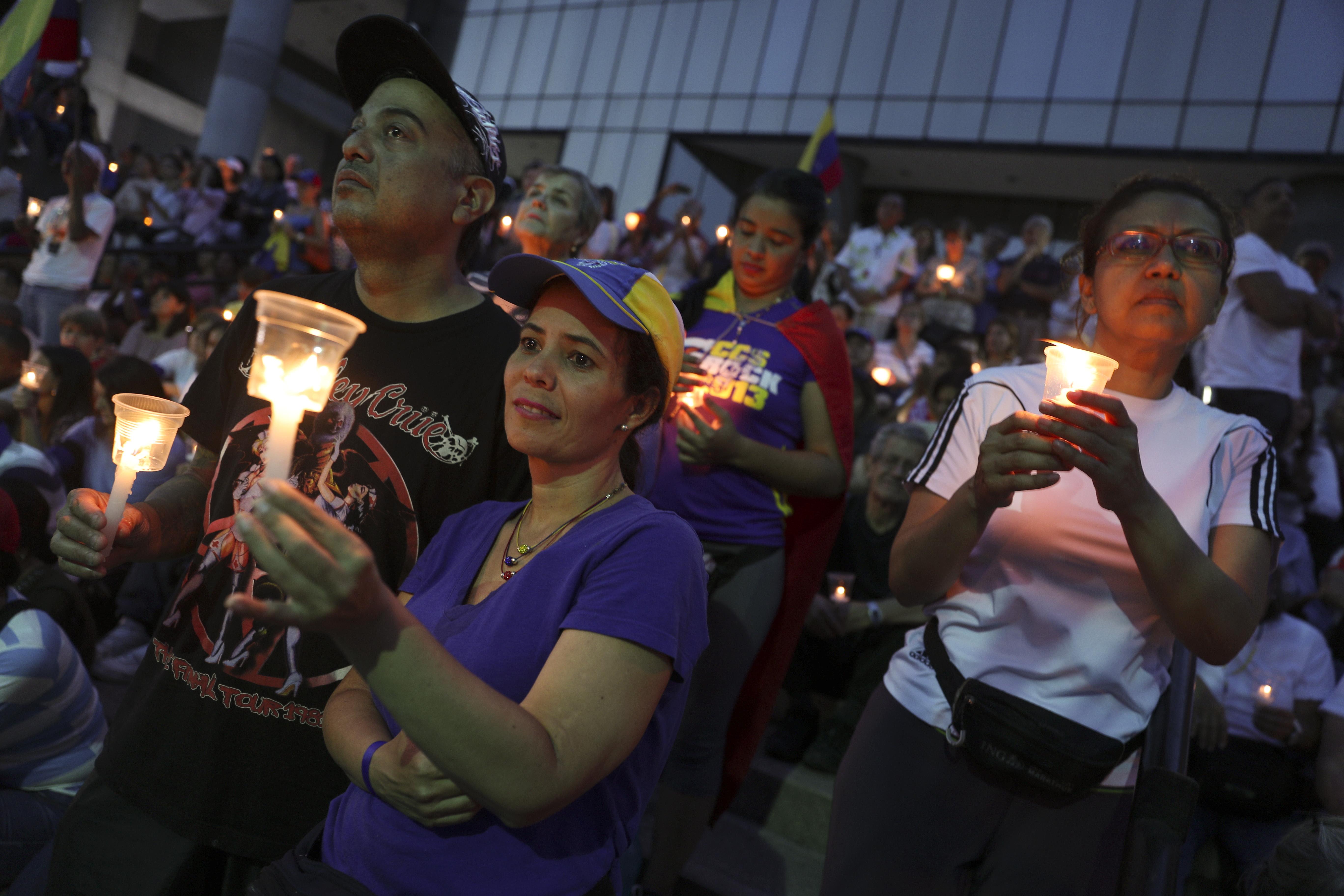 Opositores al Gobierno del presidente Nicolás Maduro sostienen velas durante una vigilia por aquellos que fallecieron en enfrentamientos la semana pasada en Caracas, Venezuela, el domingo 5 de mayo de 2019 (AP Photo/ Martin Mejia)
