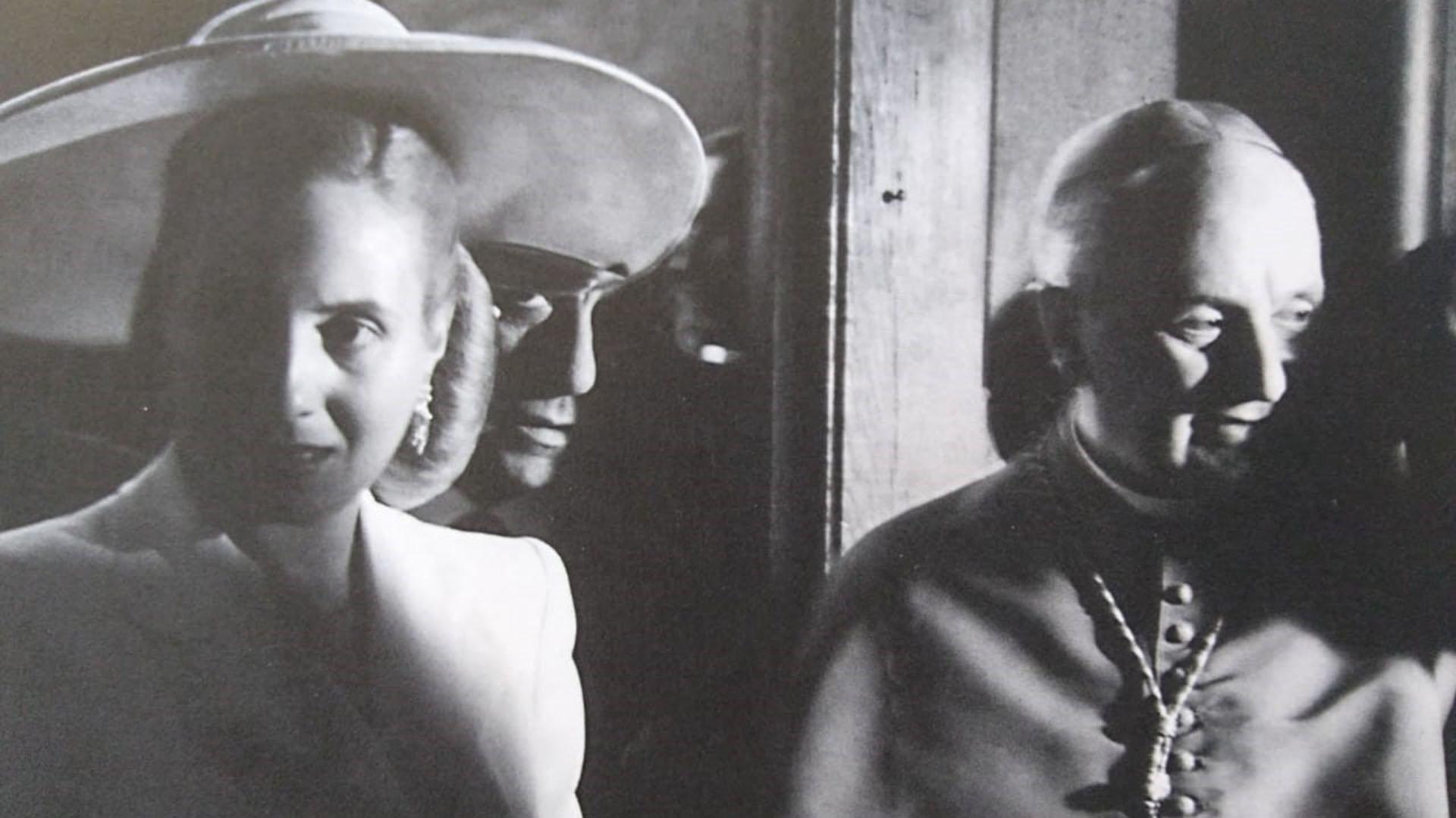 El gobierno de España la invita de manera oficial en junio de 1947. Evita emprende entonces una gira por Brasil, Uruguay, Italia, Mónaco, Suiza, Portugal y Francia. En España, le otorgan la más alta condecoración: la Gran Cruz de Isabel la Católica. En Italia, la recibe el Papa Pío XII, quien le regala el rosario de oro que llevara entre sus manos el día de su muerte. En la foto, en la Catedral de Notre-Dame en París, con el Nuncio Apostólico, Monseñor Angelo Roncalli, futuro Papa Juan XXIII
