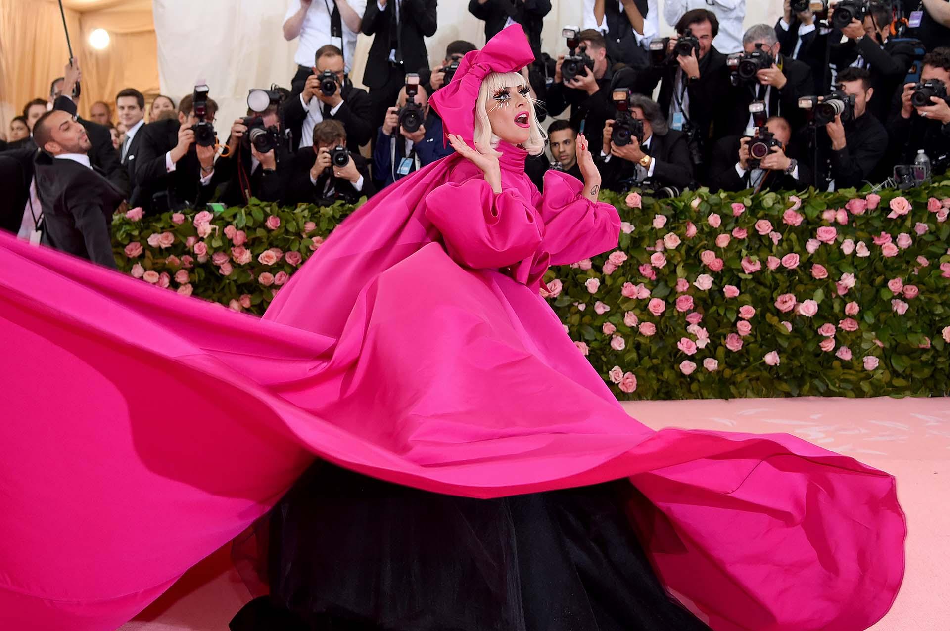 Lady Gaga es una oda al Camp. Así arribó a la alfombra rosa, con un diseño de Brandon Maxwell enfucsia neón, el primero de cuatro looks que lució la ganadora del Oscar. Fue acompañada por cinco bailarines y realizó una performance que dio inicio a la pink carpet