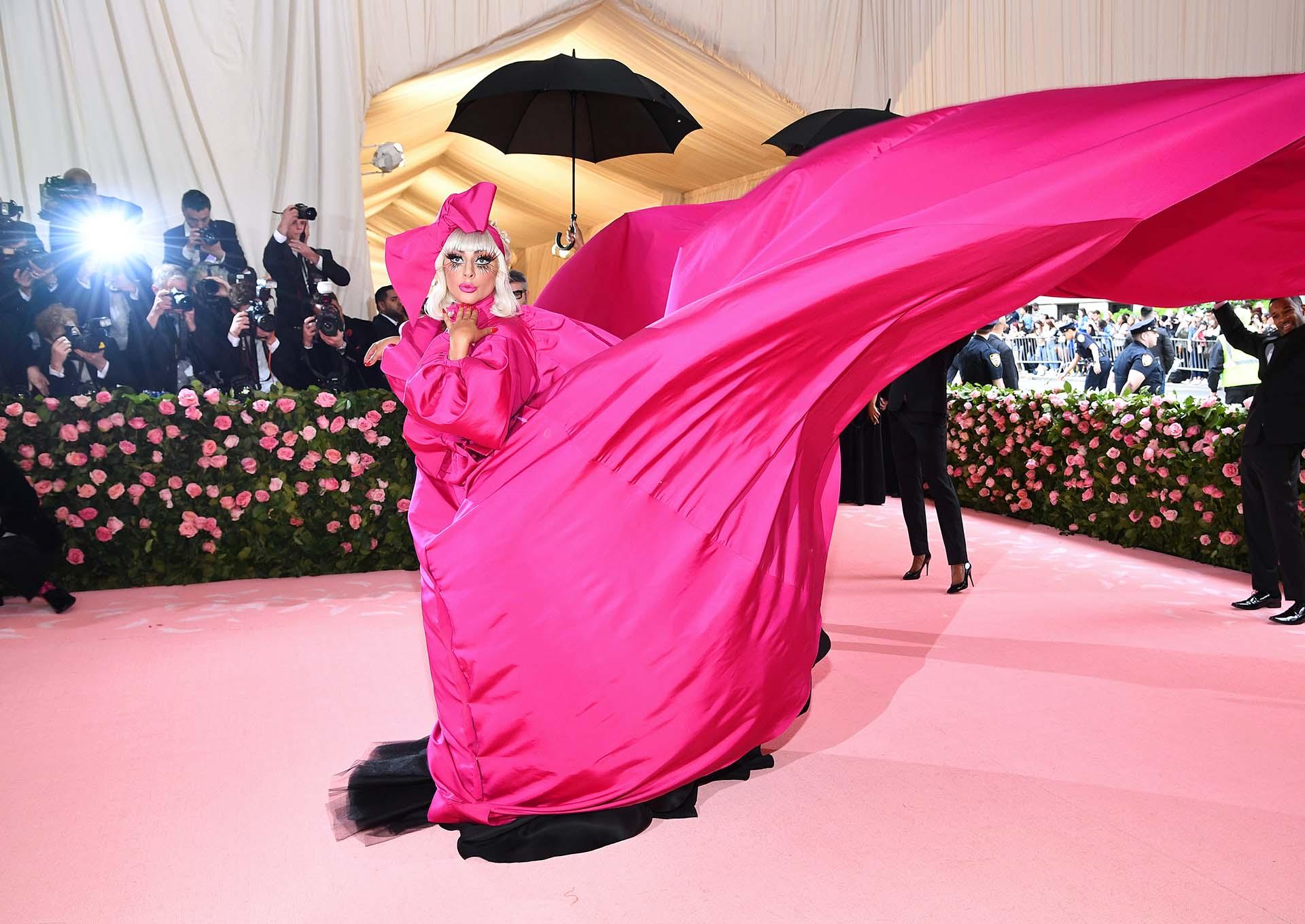 Desde la calle 84 y Madison hasta los escalones del Museo Metropolitano de Arte, Lady Gaga desfiló con cinco bailarinas,su maquilladora y su fotógrafo personal en una brillante actuación en vivo que comenzó con ella luciendo un vestido fucsia neón con una cola de siete metros y medio de largo y un moño de lazo en la cabeza