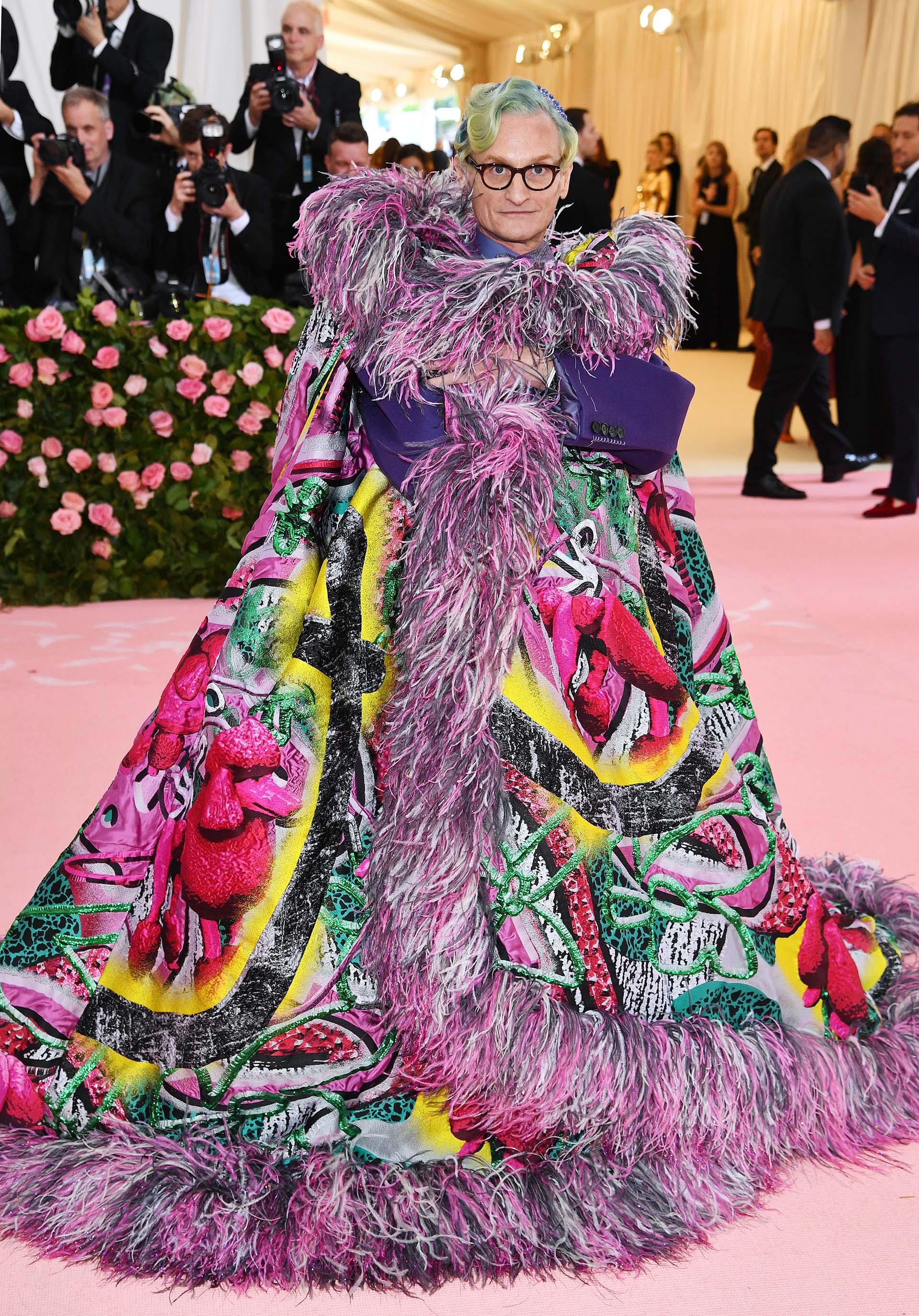 Hamish Bowles, uno de los editores de Vogue, sorprendió con una colorida capa de Maison Margiela adornada con plumas, un traje violeta y el cabello teñido de turquesa, verde y amarillo