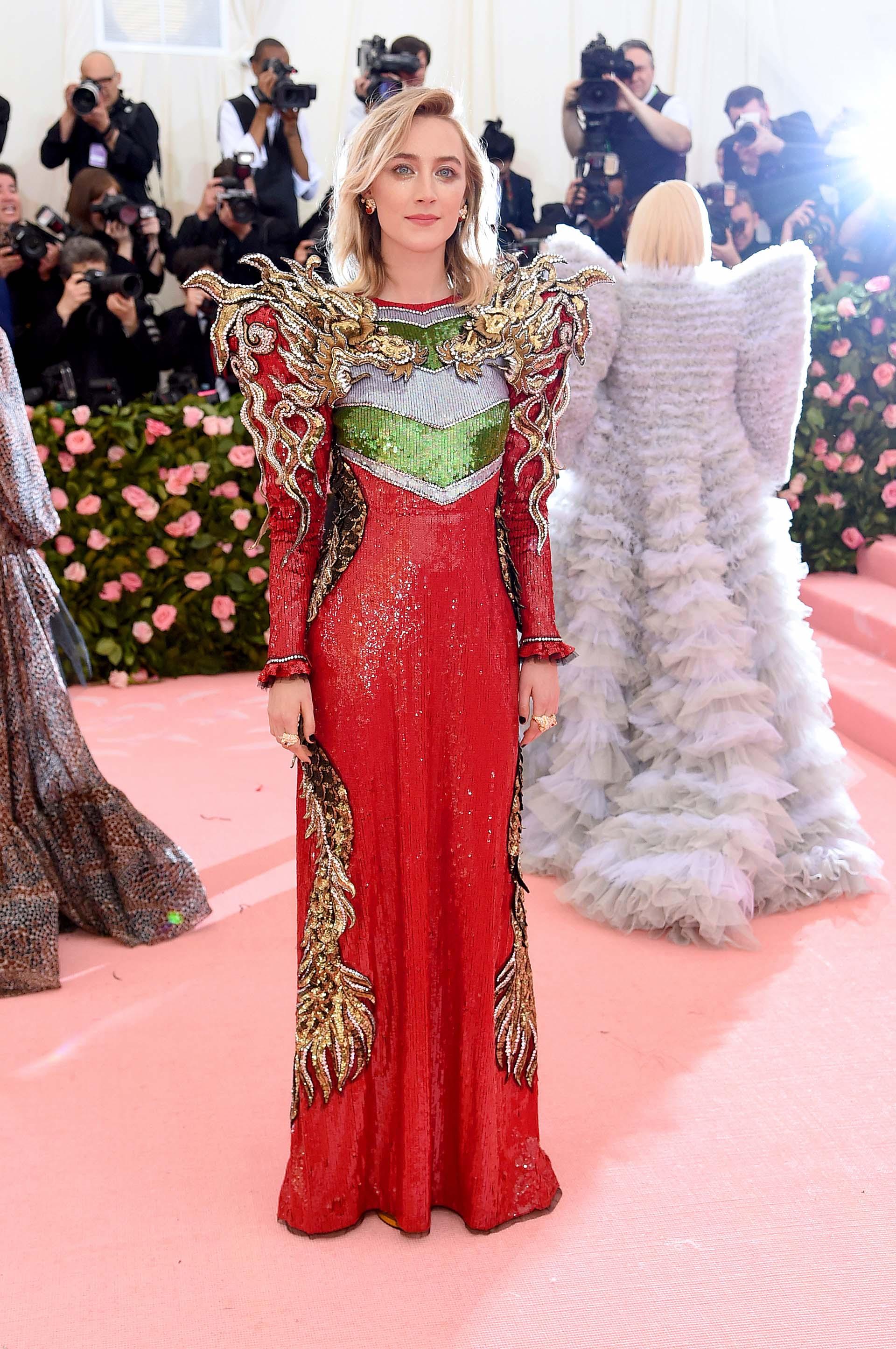 """Saoirse Ronan en un """"power suit"""" rojo, verde y dorado de hombreras y flamas de fuego"""