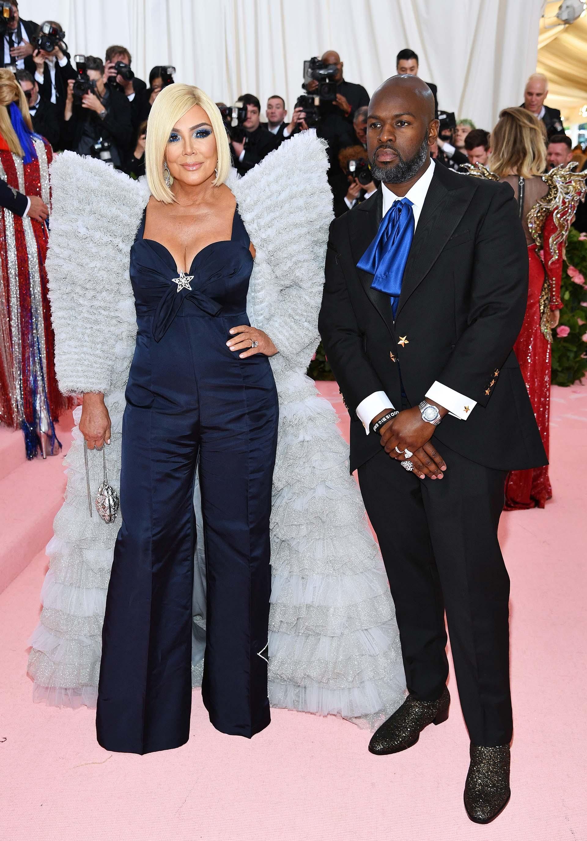 Kris Jenner acompañada por su pareja Corey Gamble, esta vez conel cabello rubio, optó por un traje azul noche y una capa color pastel