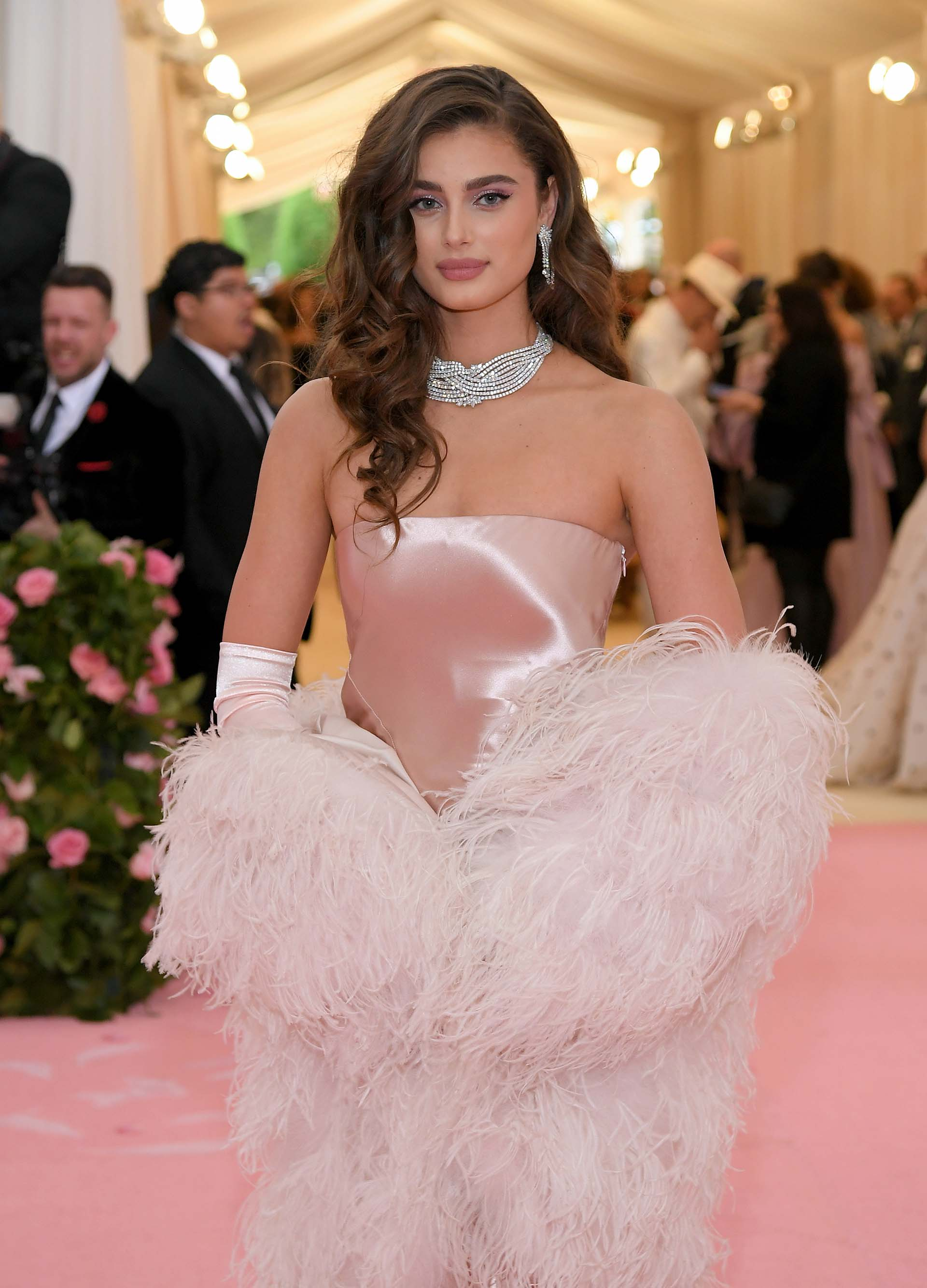 Quizás un poco clásica, Taylor Hill lució un vestido strapless rosa que acompañó con una chaqueta de plumas en el mismo color