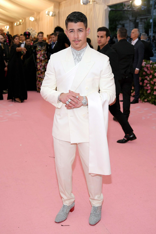 Nick Jonas, también con un look de Dior, apostó a los brillos, a las jojas y al maquillaje para darle un tono camp a su traje blanco