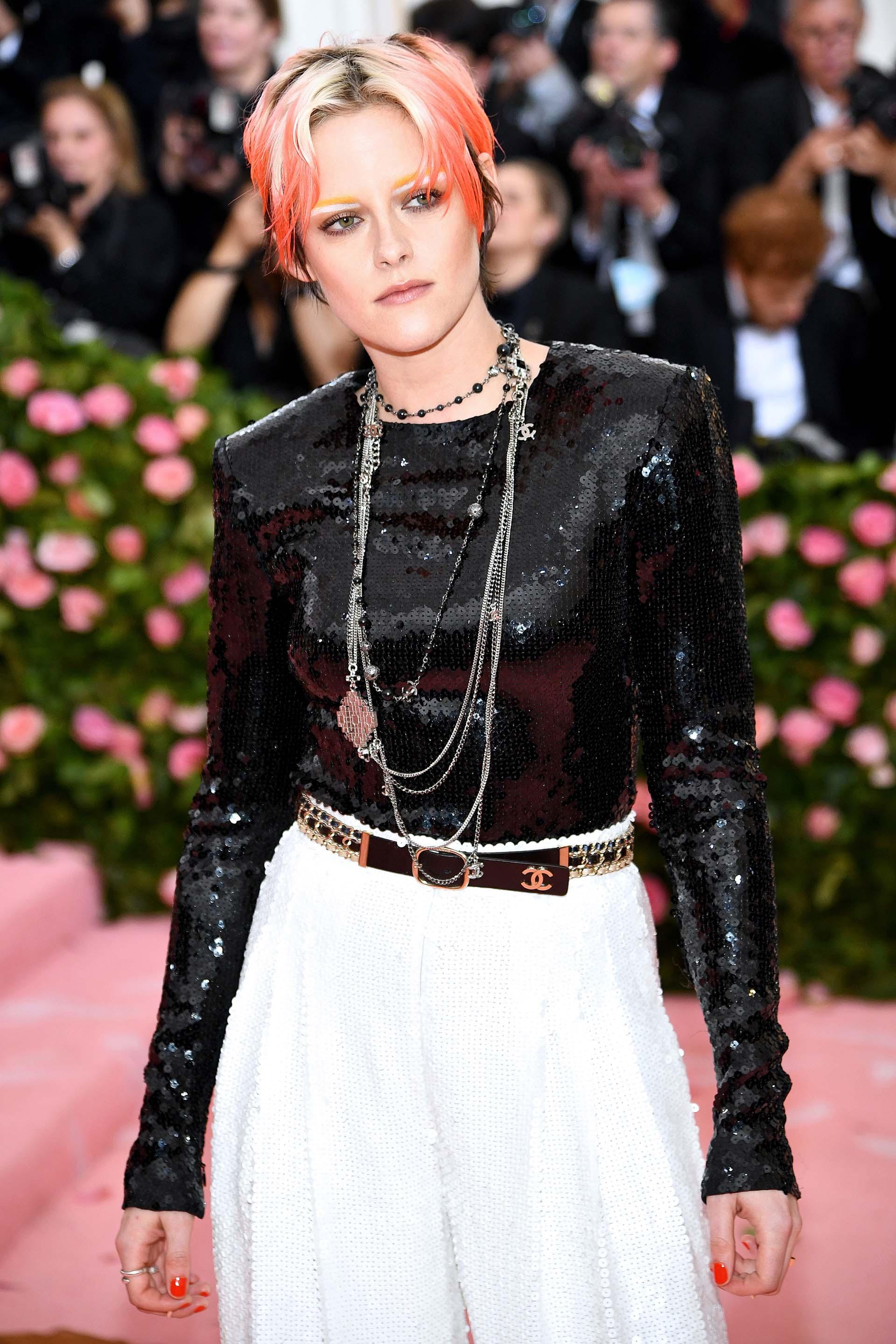 Kristen Stewartlucióun top negro y un pantalon de traje blanco de lentejuelas que acompañó con joyas y un cinturón Chanel