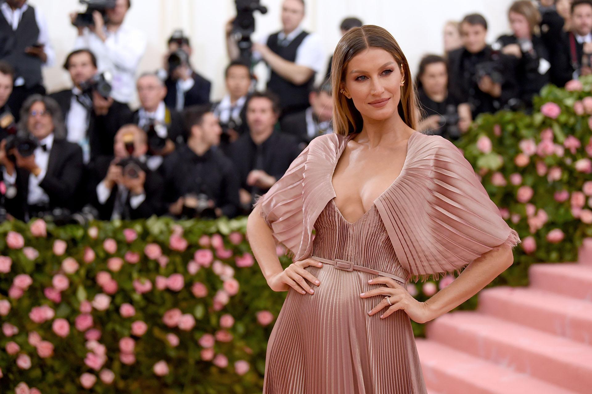 Gisele Bündcheny su marido Tom Brady asistieron a su 11° MET Gala juntos. La supermodelo optó por un clásico vestido plisado color rosa Dior 100% sustentable