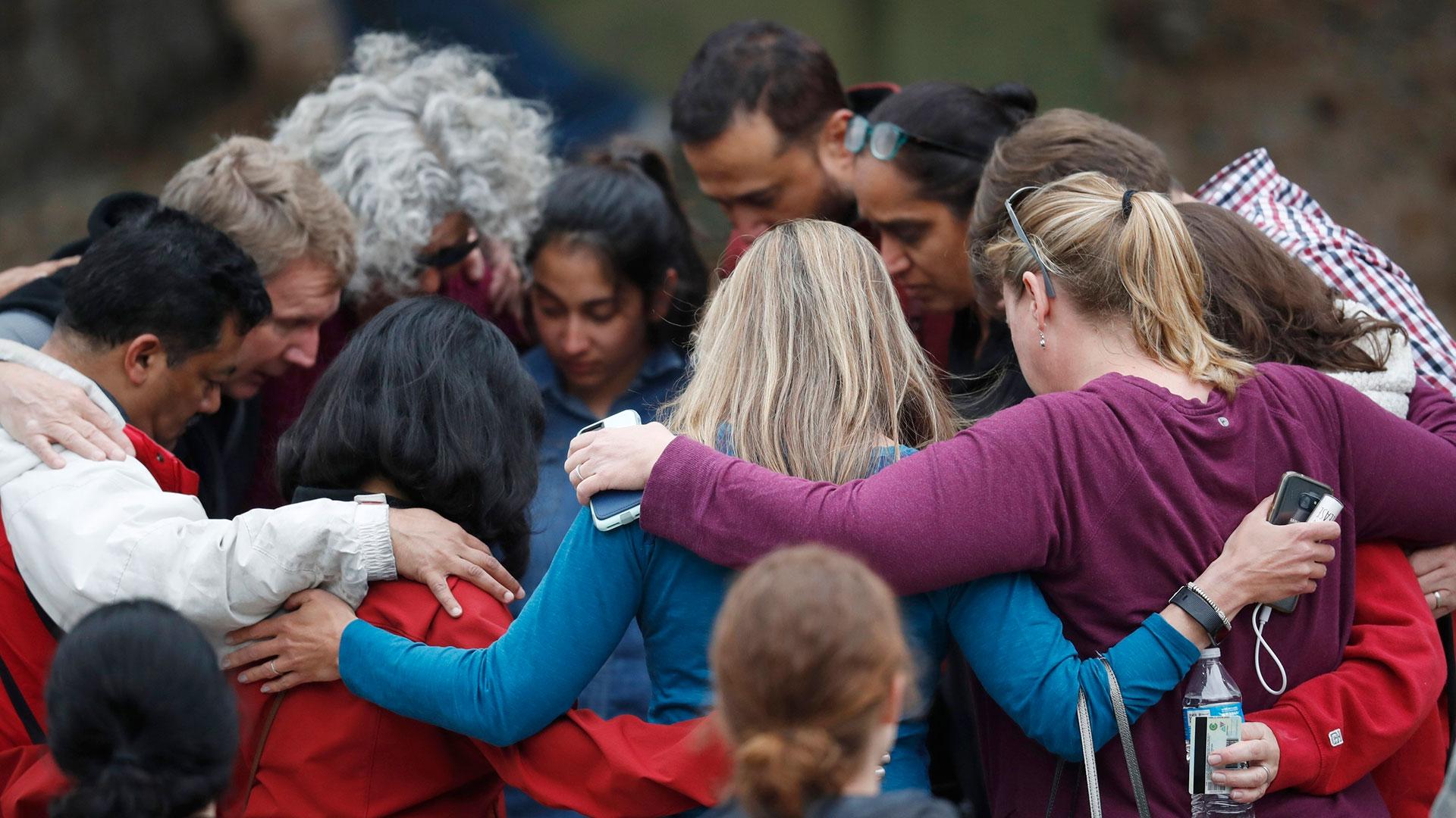 Familiares de las víctimas se abrazan en la puerta de la escuela (AP)