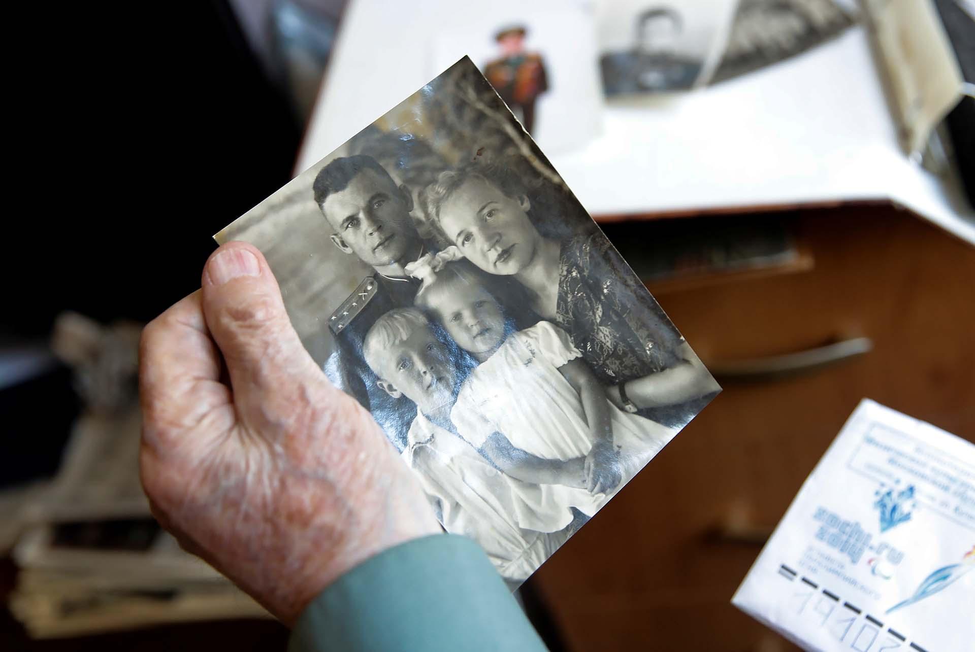 Nikolay Bagayev con una antigua foto de él junto a su esposa y sus dos hijos (REUTERS/Maxim Shemetov)