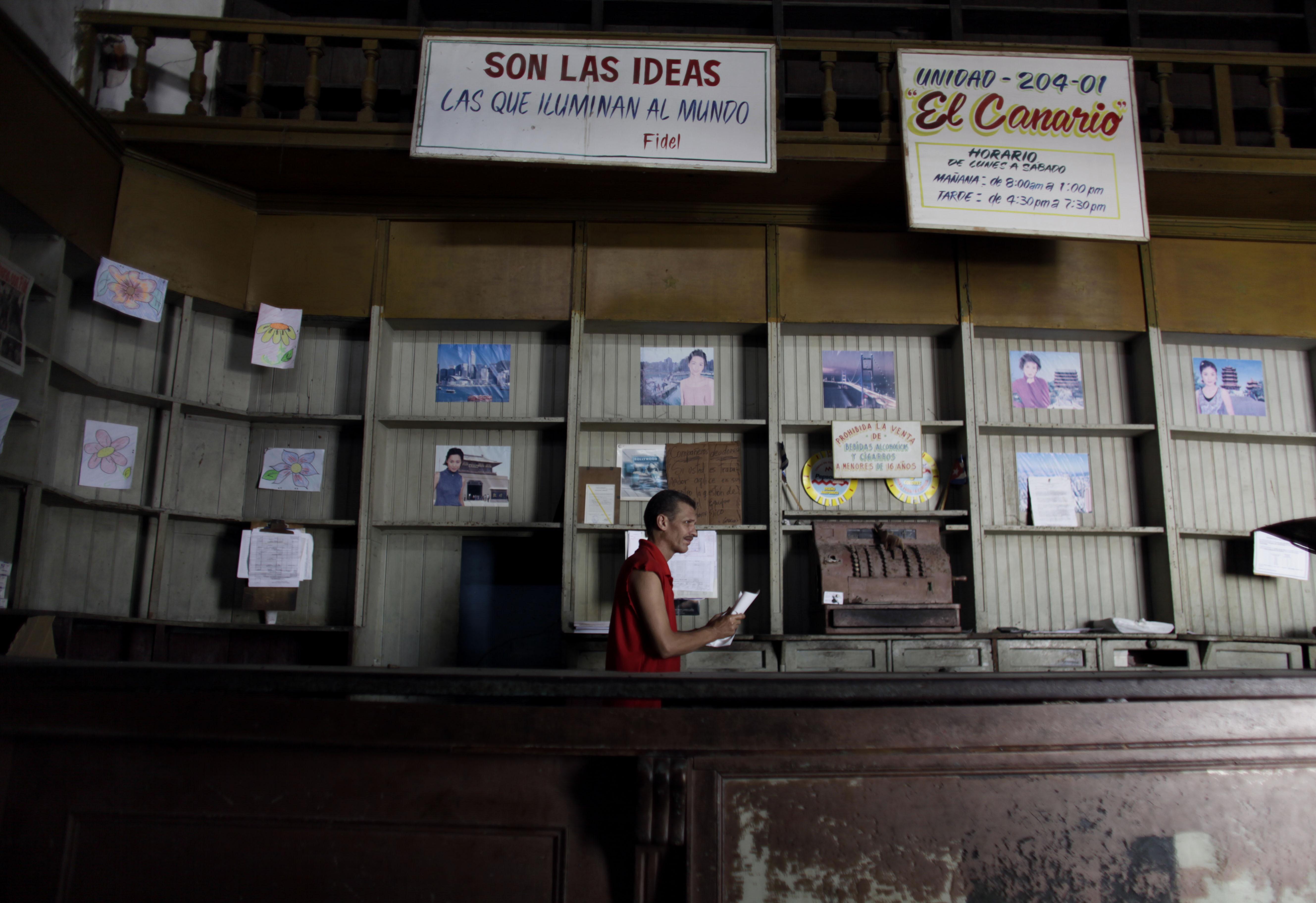 ARCHIVO – En esta fotografía de archivo del 9 de octubre de 2009, un empleado trabaja en una tienda de alimentos del gobierno que tiene los anaqueles vacíos, en La Habana, Cuba. (AP Foto/Javier Galeano, archivo)